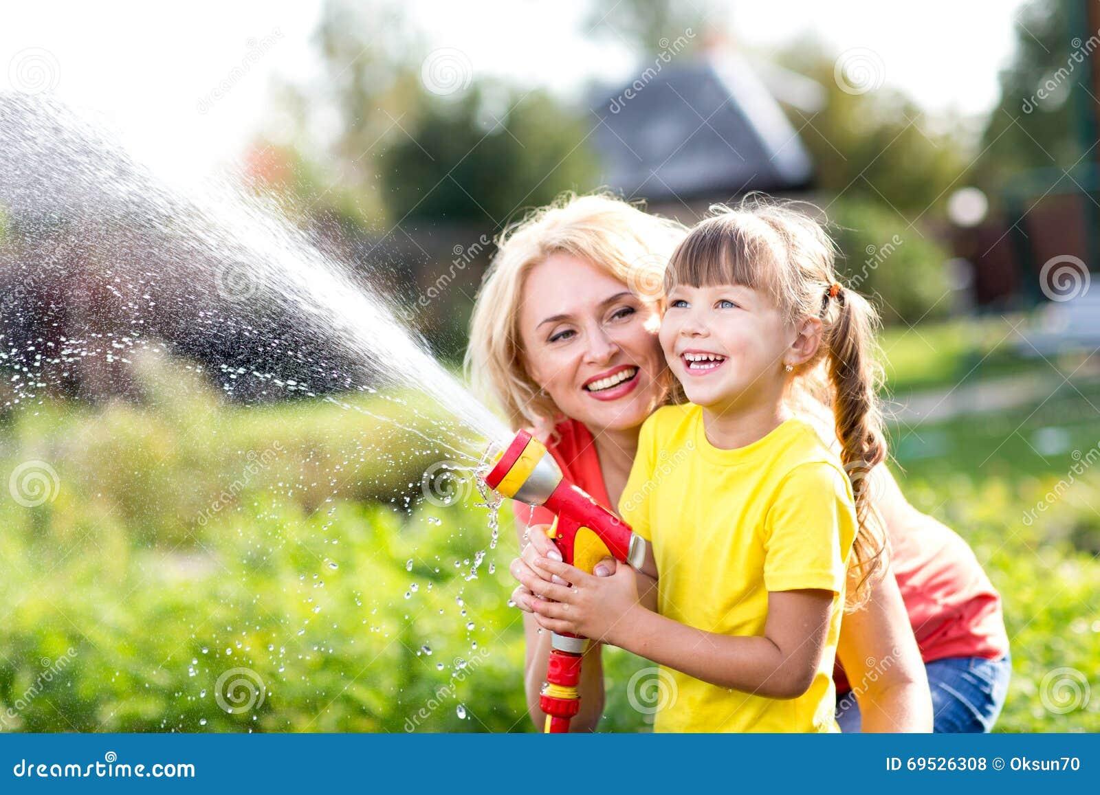 Liten trädgårdsmästareflicka med modern som bevattnar på near hus för gräsmatta