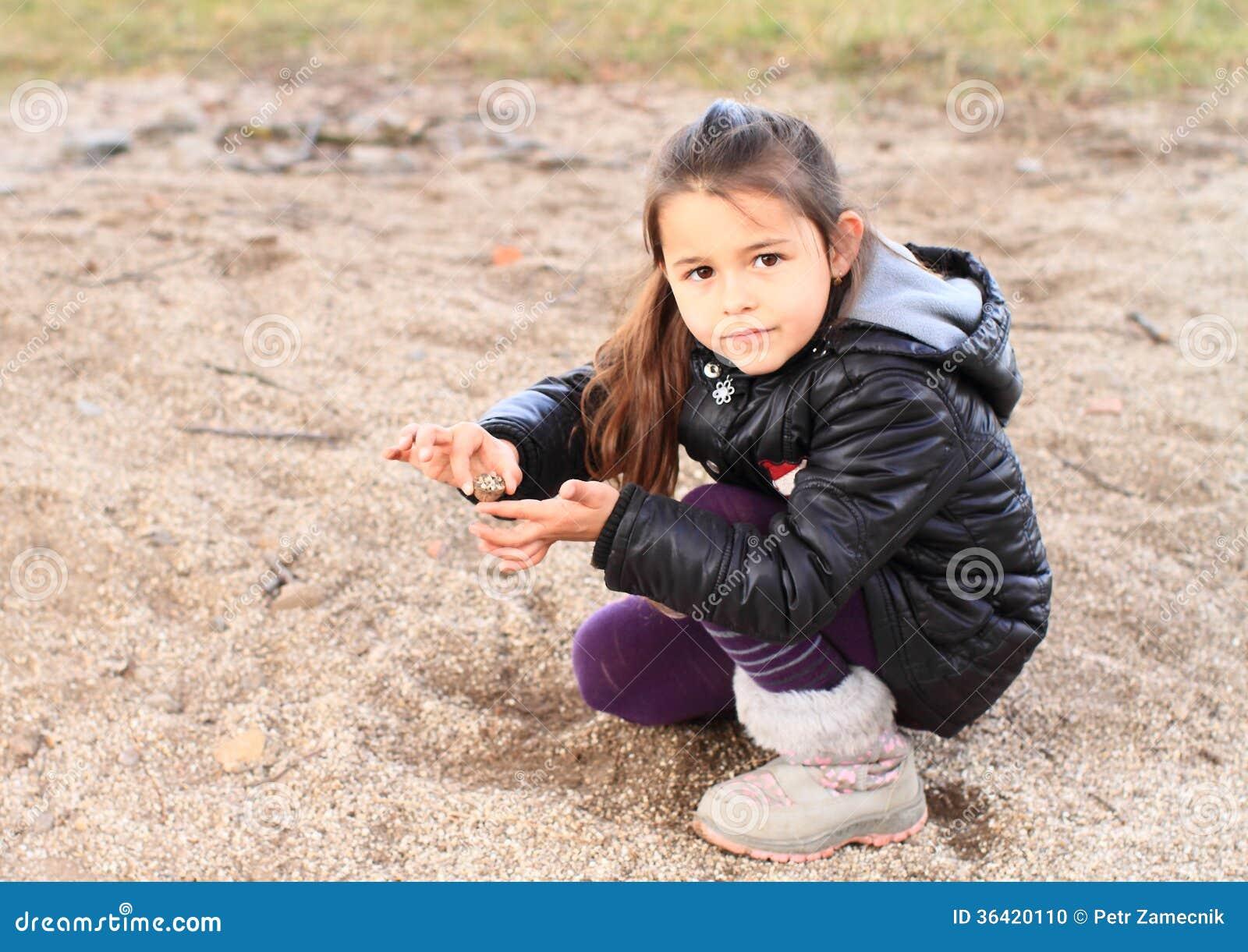 Liten unge - flicka som spelar i sand