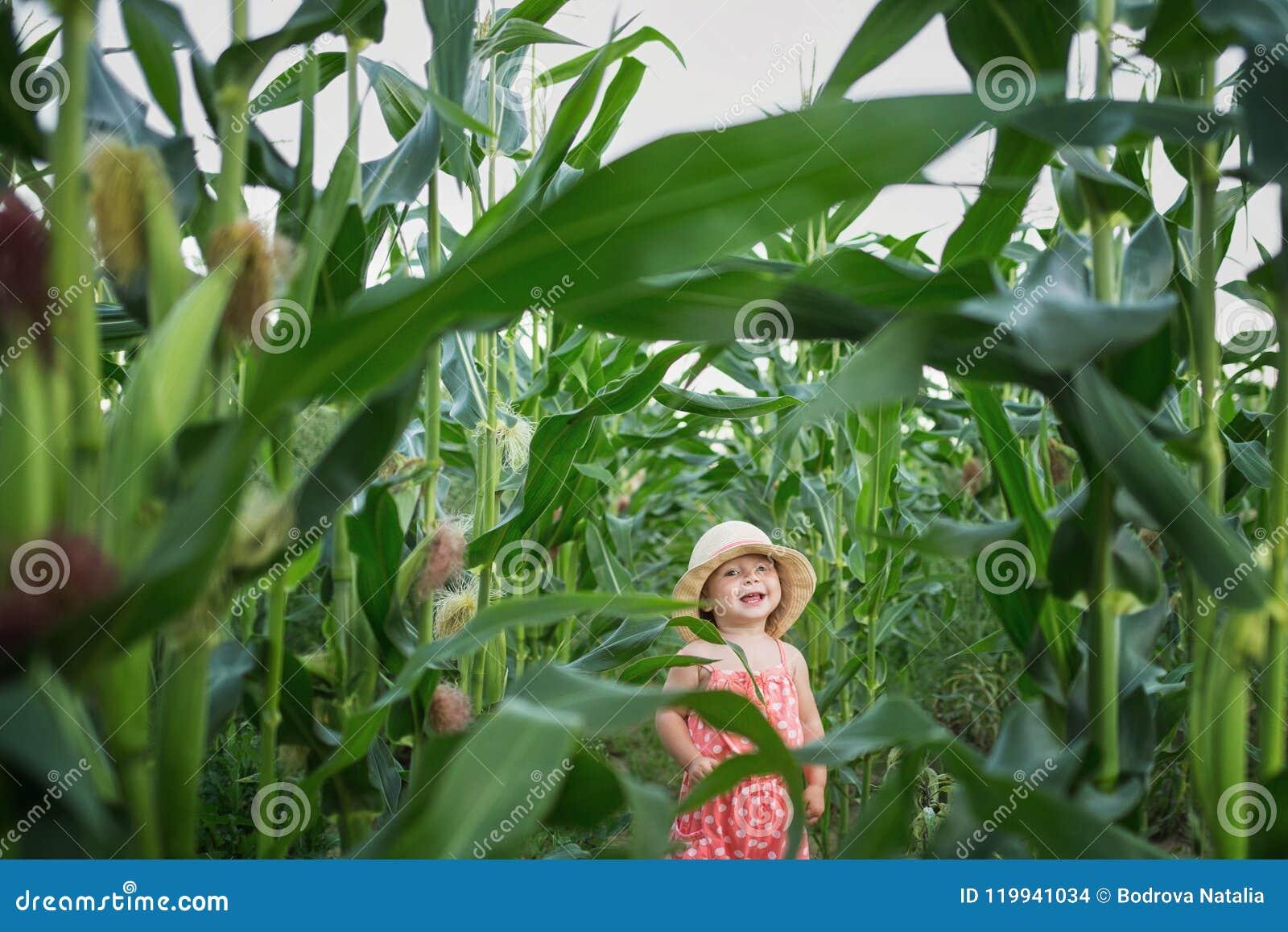 Liten unge i en hatt som skrattar i mitt av ett havrefält