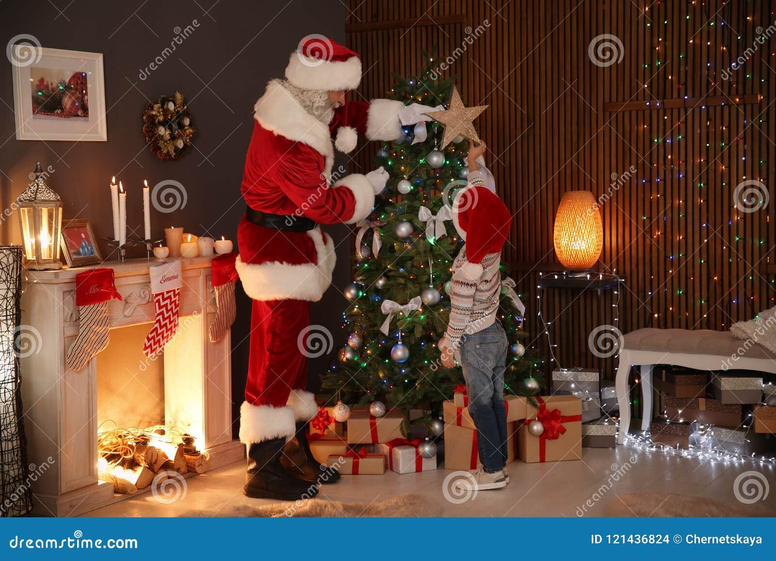 Litet barn med Santa Claus som överst sätter julgranen för stjärna hemma