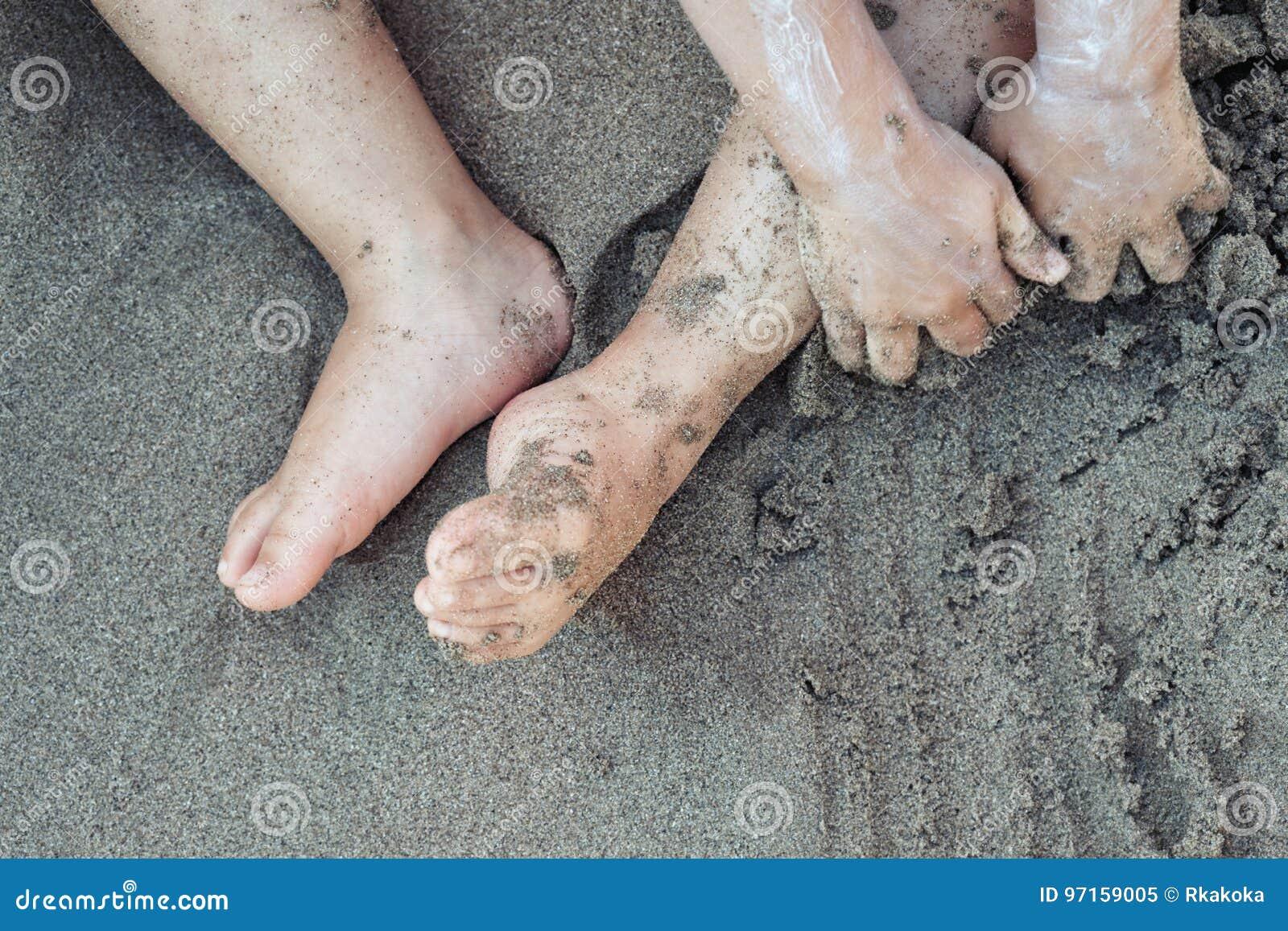 Litet barnbarn som spelar i strandsanden med sunscreen sikt för bakgrunder för ferie för strand för familj på för slut för abstra