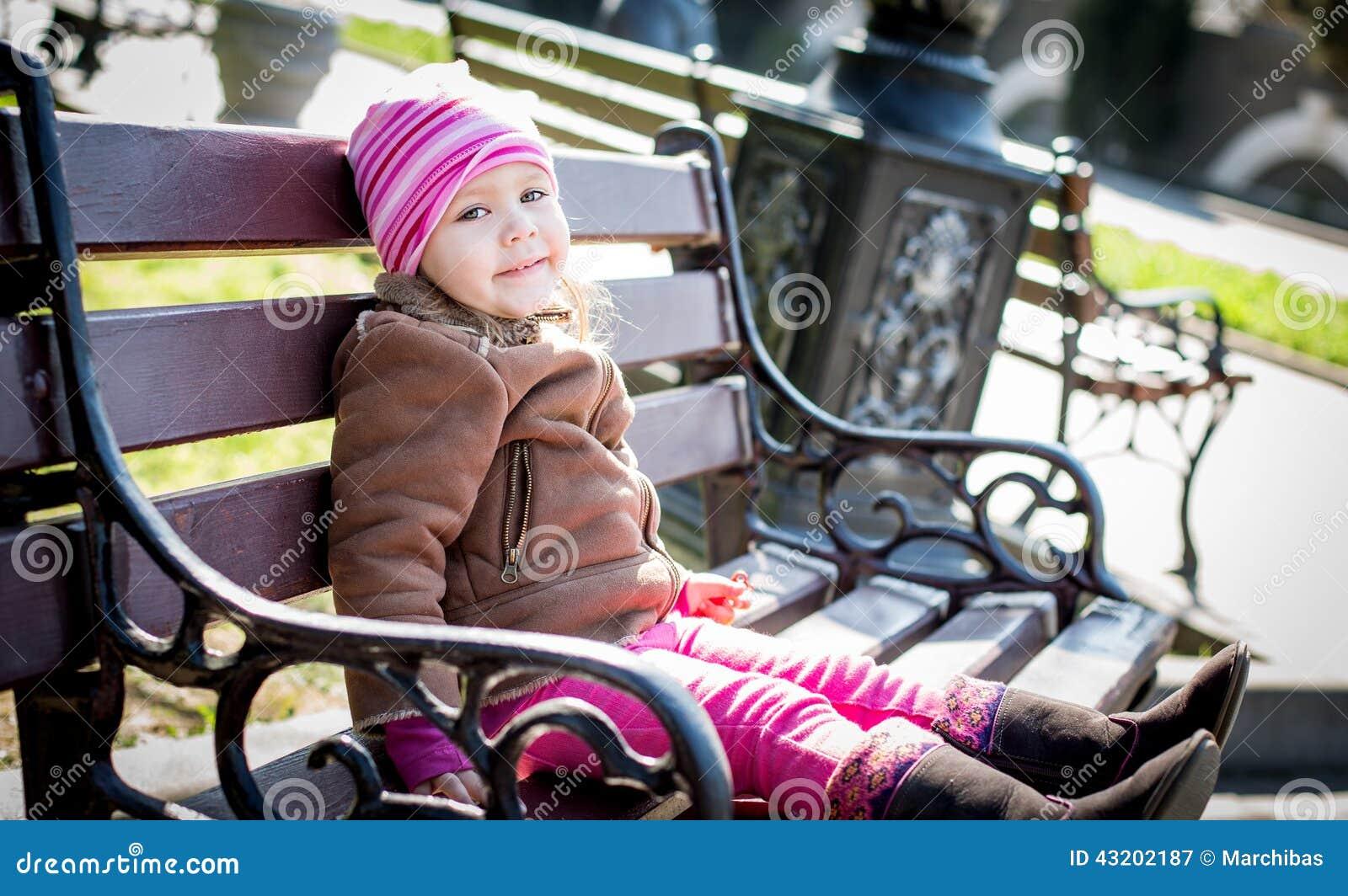 Download Litet Barnflickasammanträde På Bänken Fotografering för Bildbyråer - Bild av folk, avkommor: 43202187
