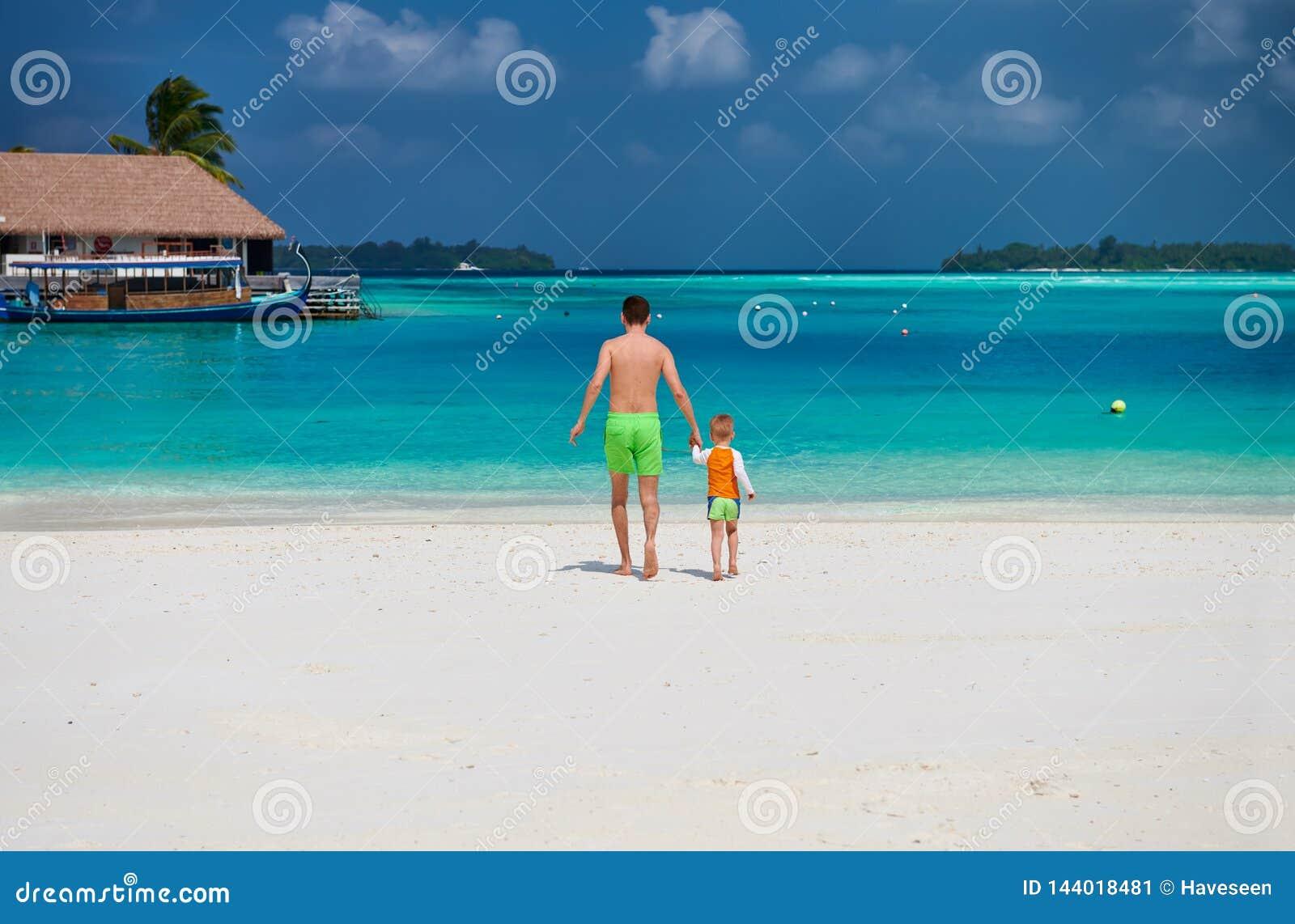 Litet barnpojke på stranden med fadern