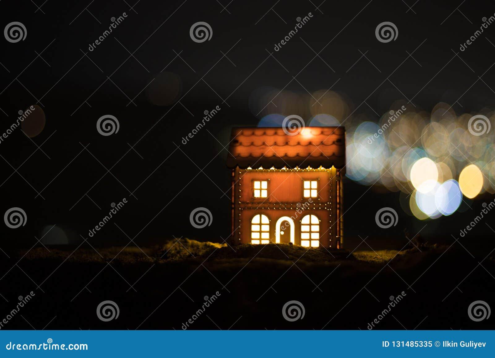Litet dekorativt hus, härlig festlig stilleben, gulligt litet hus på natten, bakgrund för bokeh för nattstad verklig, lycklig vin