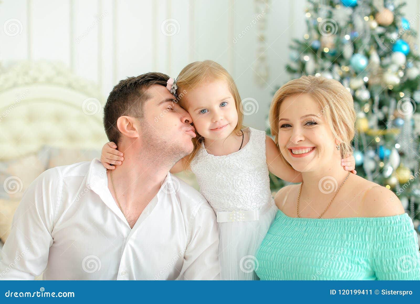 Litet dottersammanträde med den kyssande fadern och den blonda modern nära dekorerade julgranen