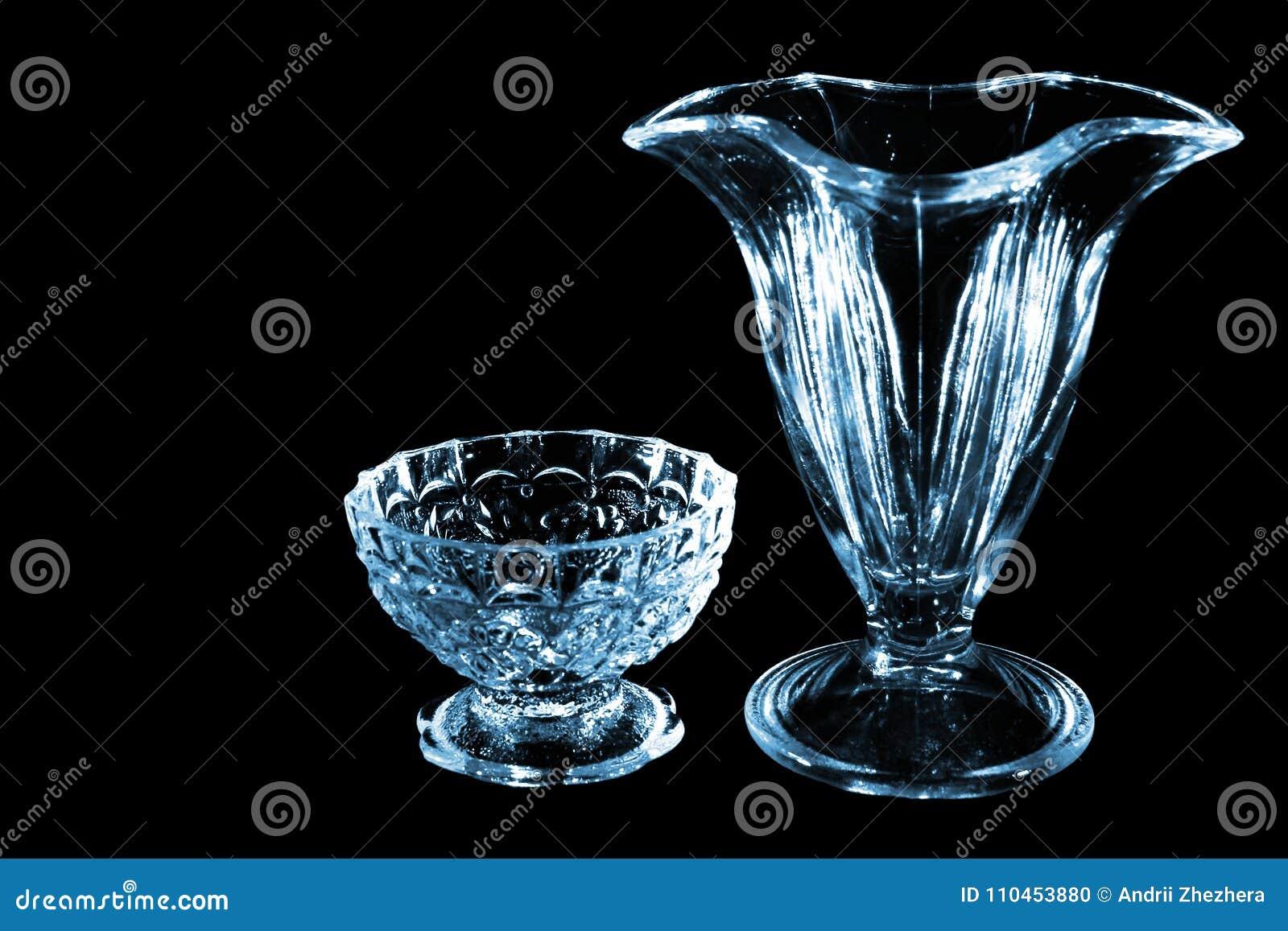 Litet exponeringsglas och vas som isoleras på svart bakgrund