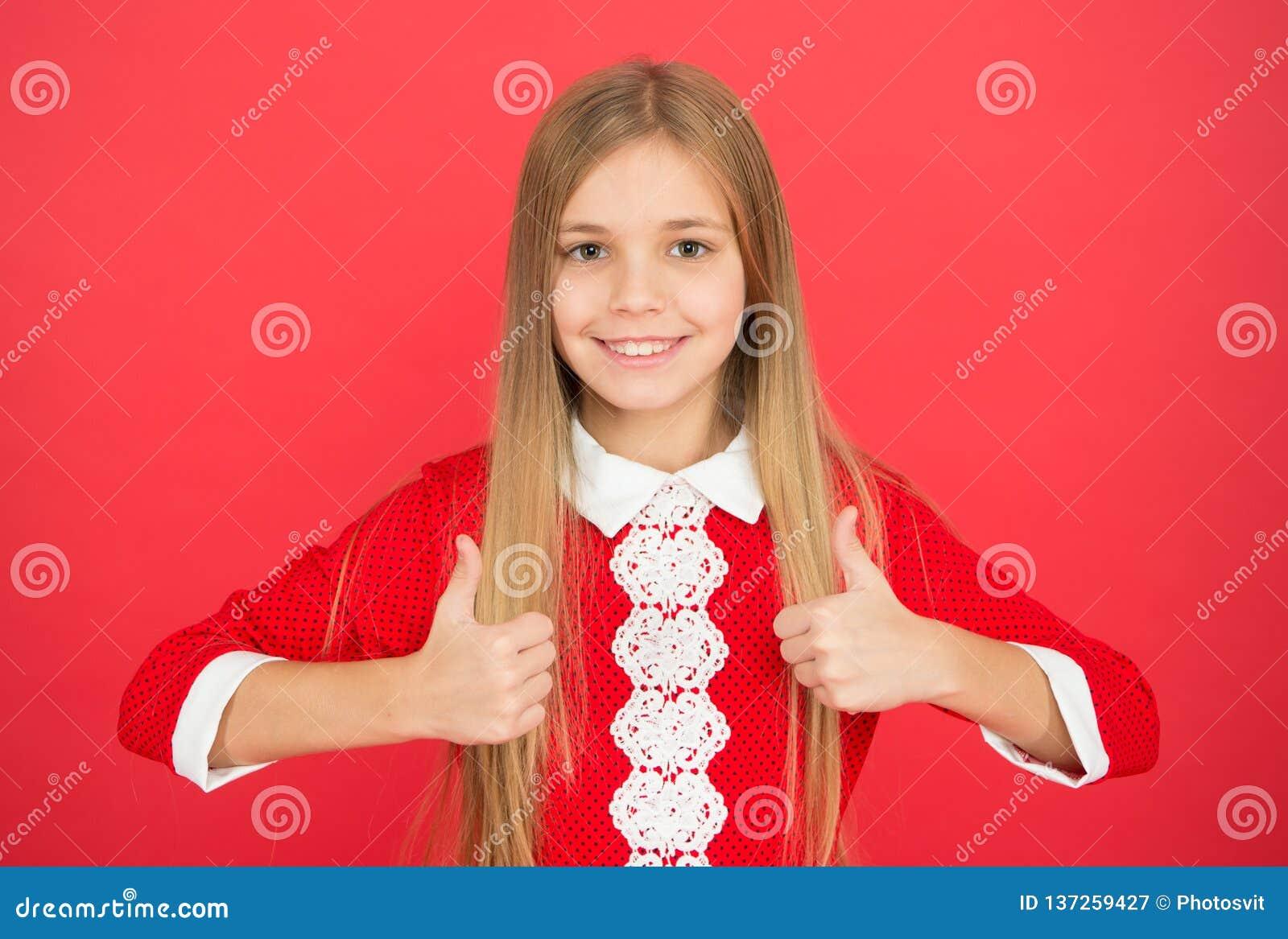 Litet flickabarn Skolutbildning lycklig liten flicka på röd bakgrund Familj och förälskelse Barns dag Barndom