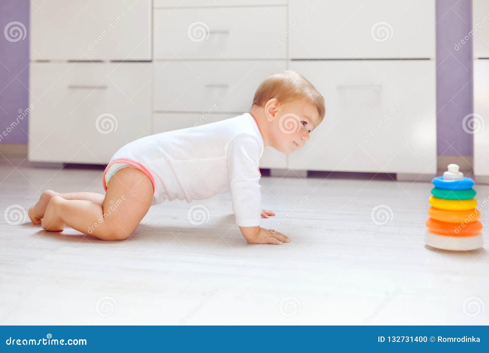 Litet gulligt behandla som ett barn flickan som lär att krypa Sund barnkrypning i ungerum Le den lyckliga sunda litet barnflickan