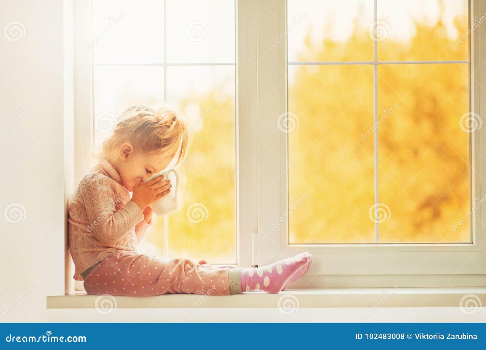 Litet gulligt ungeflickasammanträde vid den inomhus innehavkoppen för fönster av varm drinkkakao som tycker om höstskogbakgrund S
