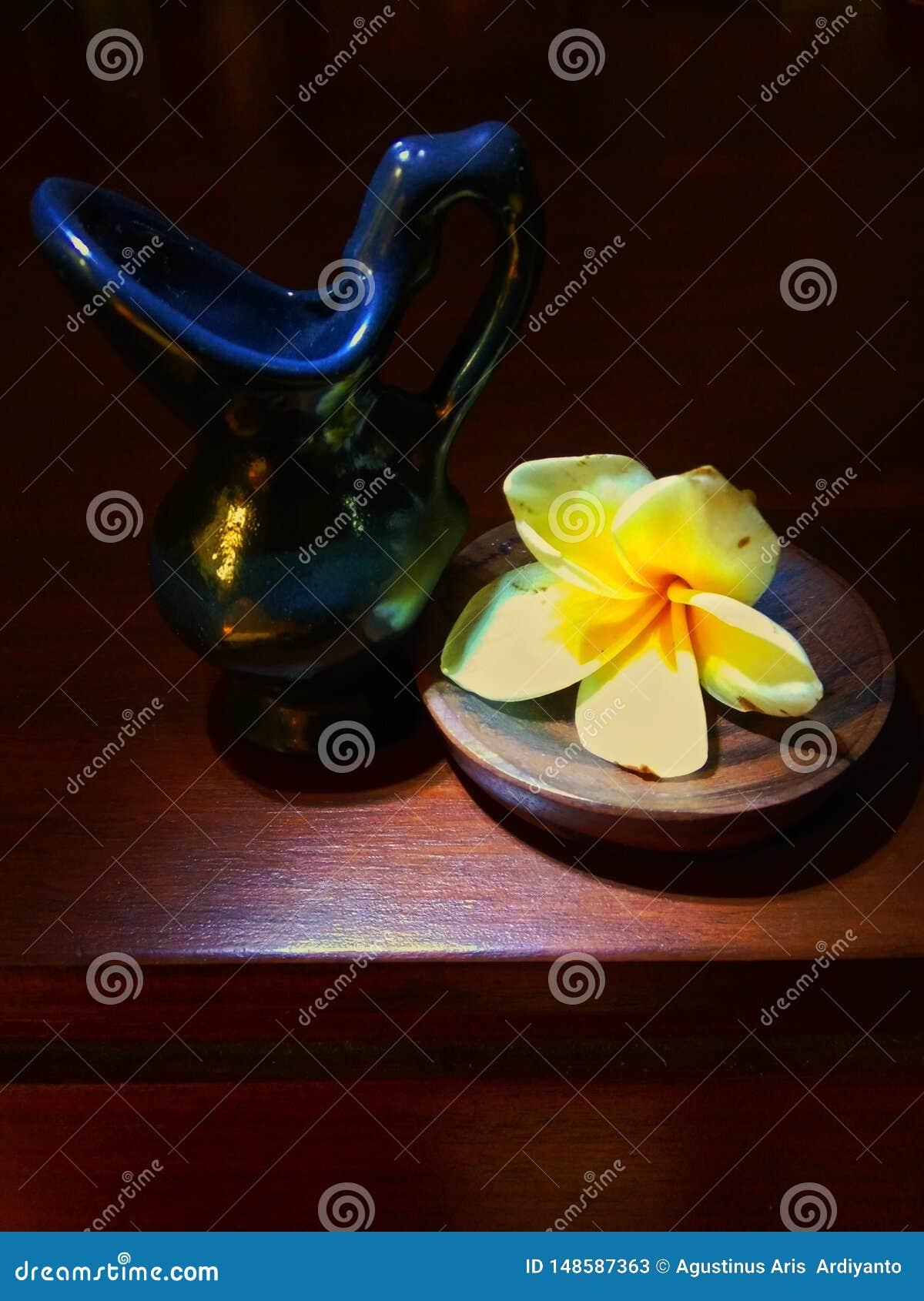 Litet keramiskt med frangipaniblommor