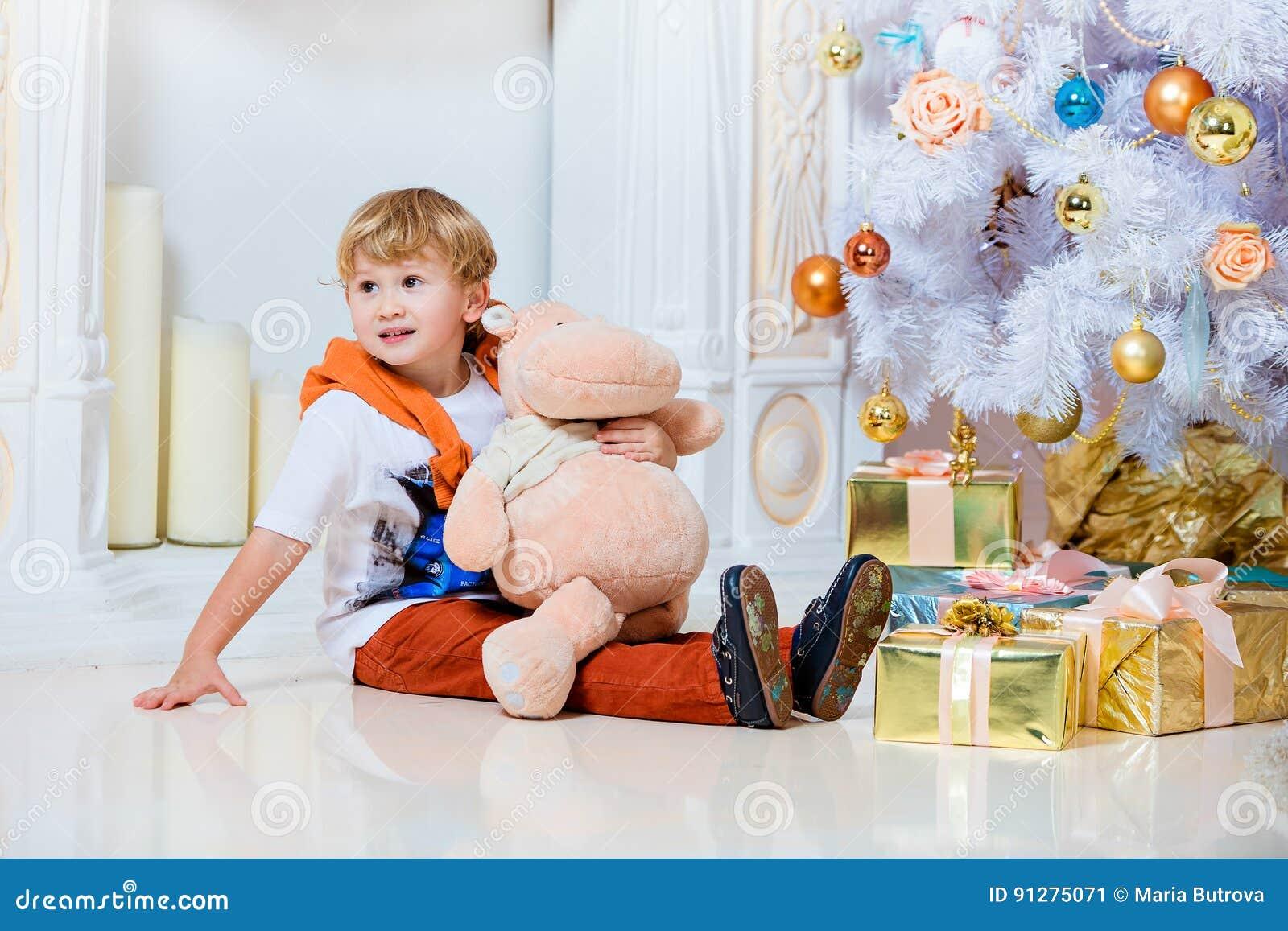 Litet mycket gulligt blont pojkesammanträde vid spisen och viten Chr