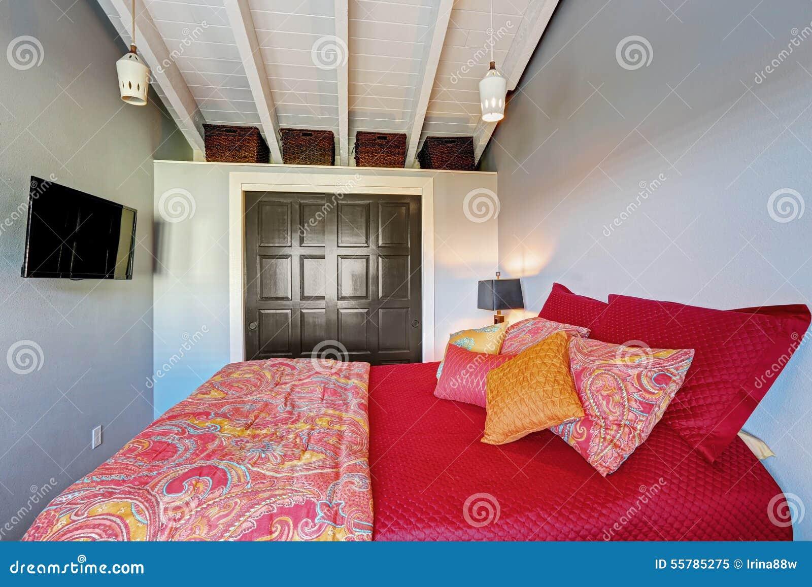Litet perfekt sovrum med röd sängkläder och gråa väggar arkivfoto ...