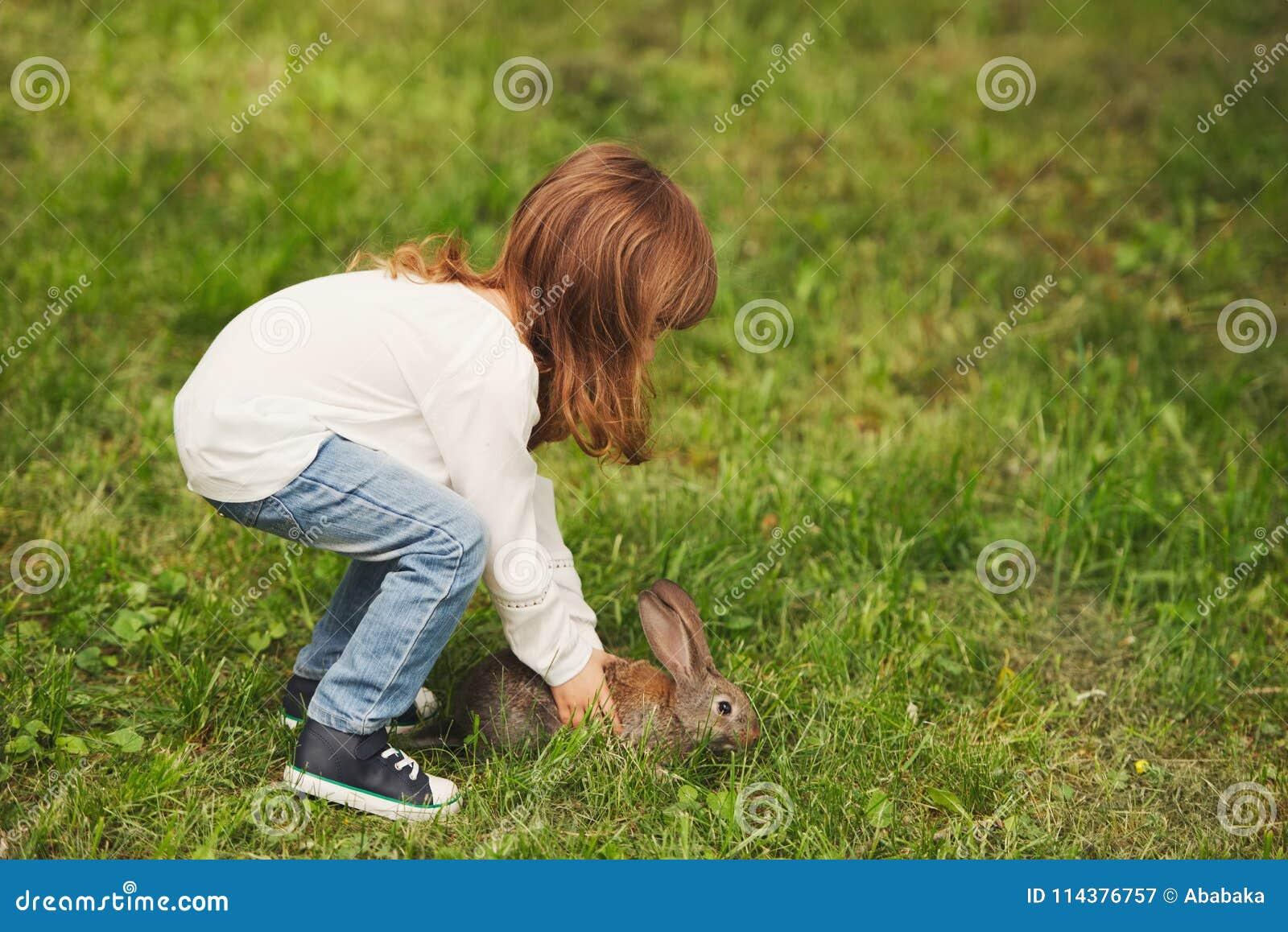 Litle男孩戏剧用兔子在公园