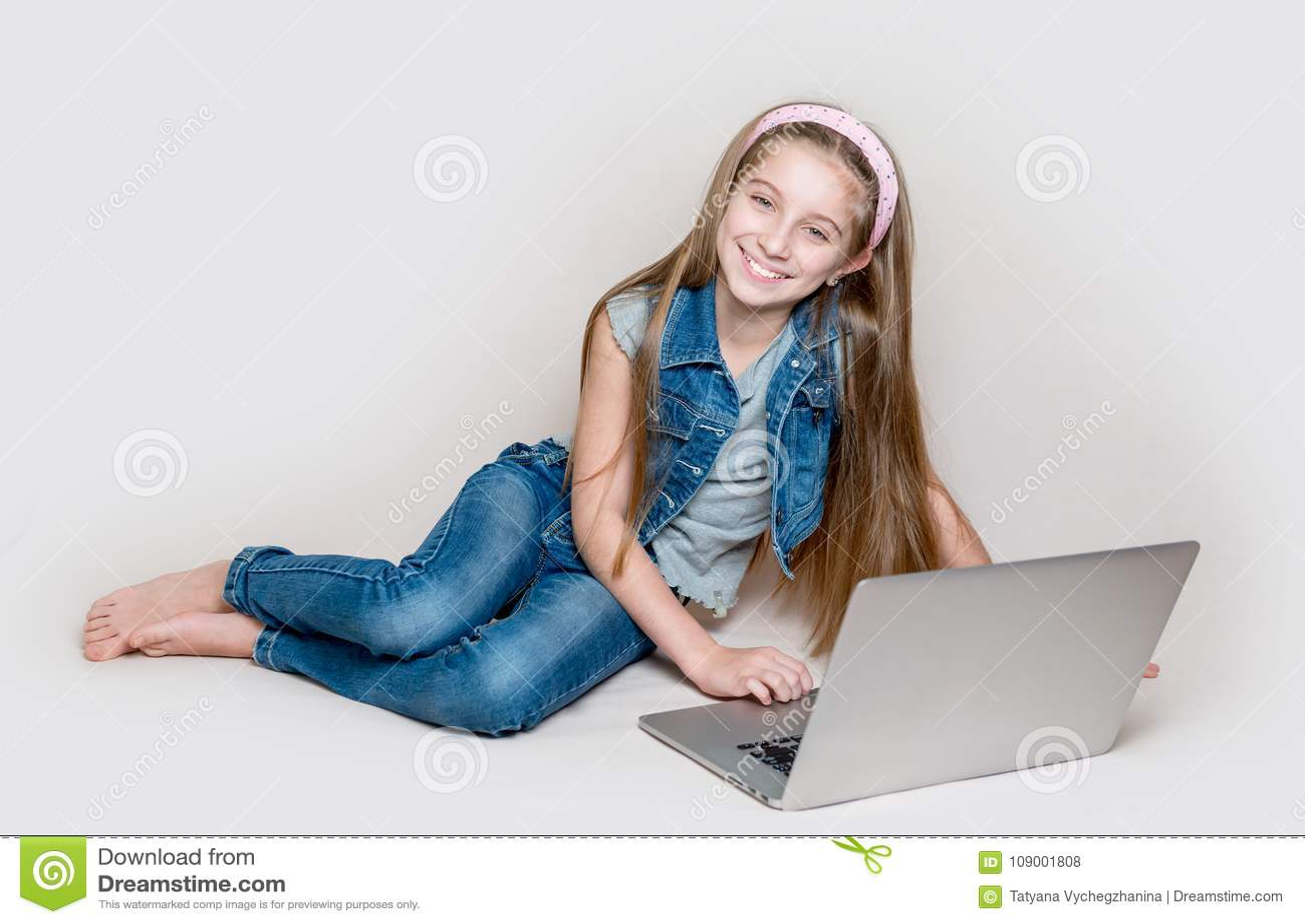 Litllemeisje die op vloer met laptop liggen