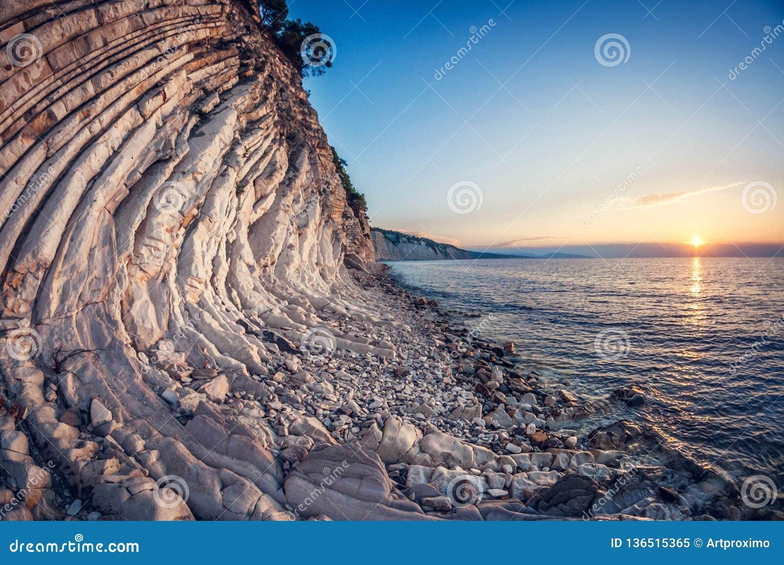 Litoral mergulhado rochoso branco da paisagem no por do sol, distorção do fisheye