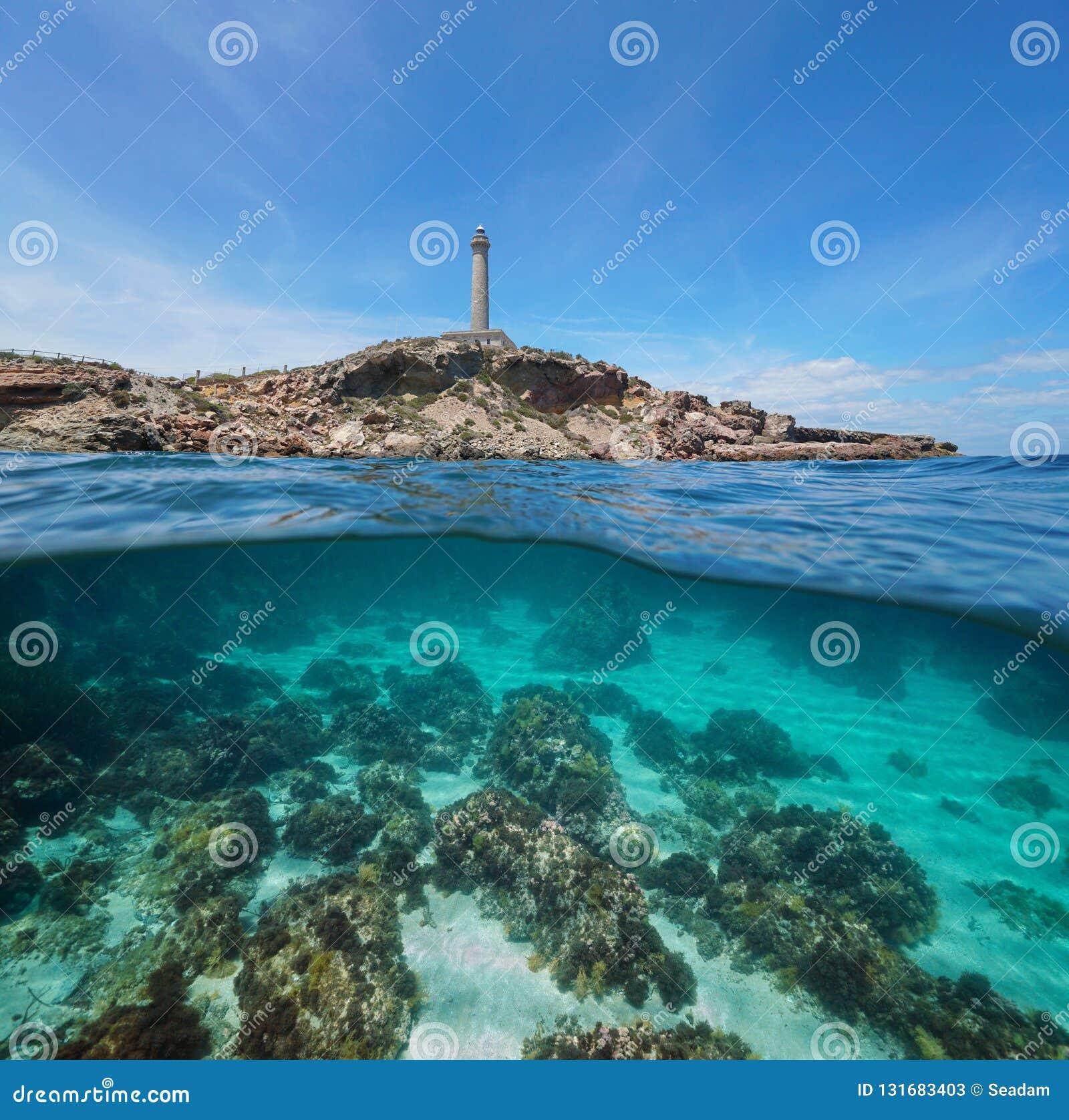 Litoral rochoso com um farol e um fundo do mar com rochas e uma areia subaquática