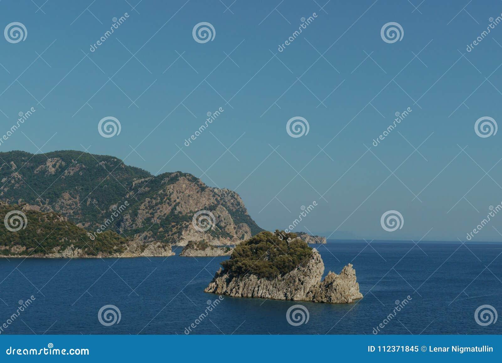 Litoral rochoso, ilha no tempo claro