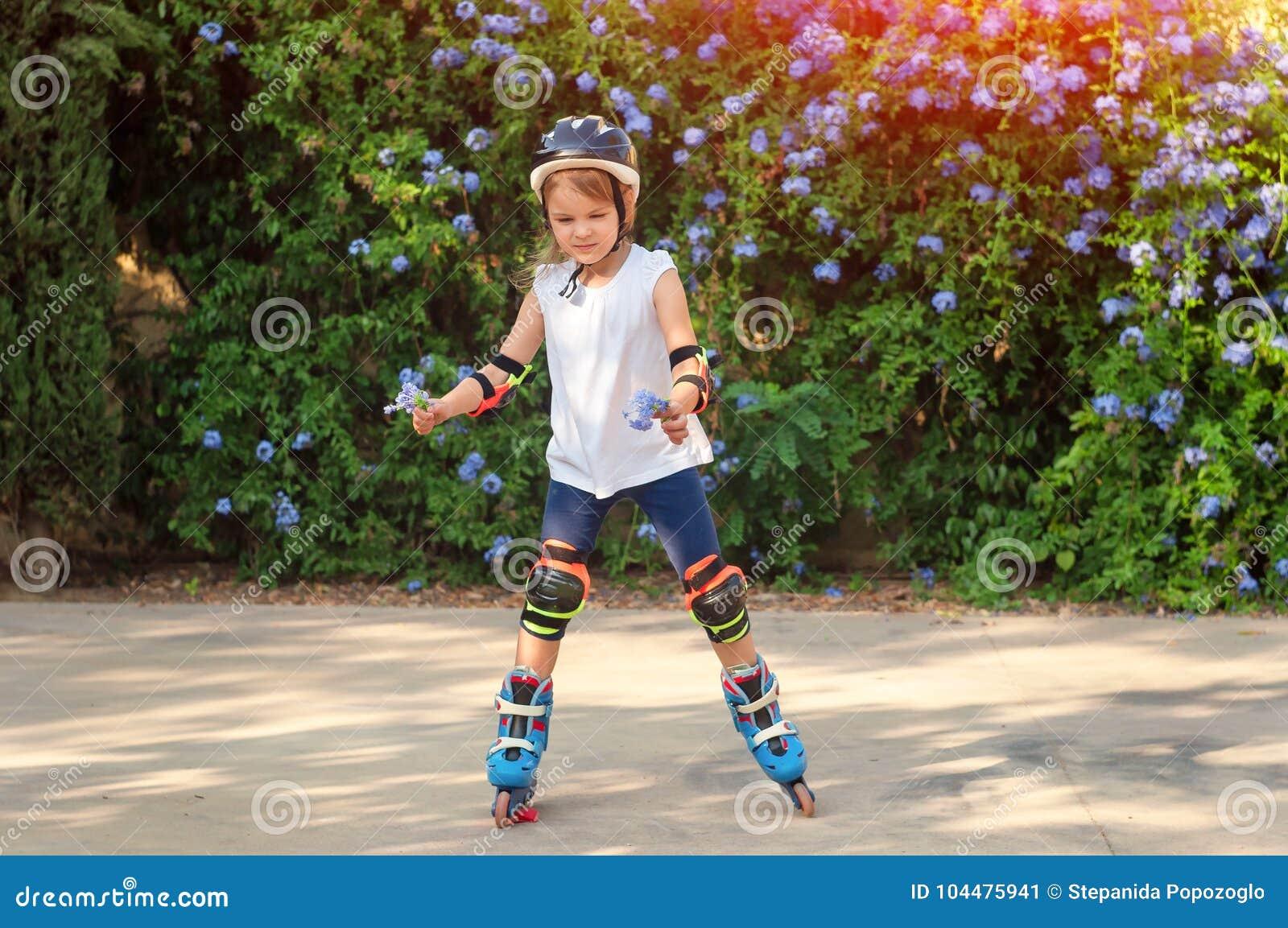 Littl dziewczyna na rolkowych łyżwach w hełmie przy parkiem w rękach,