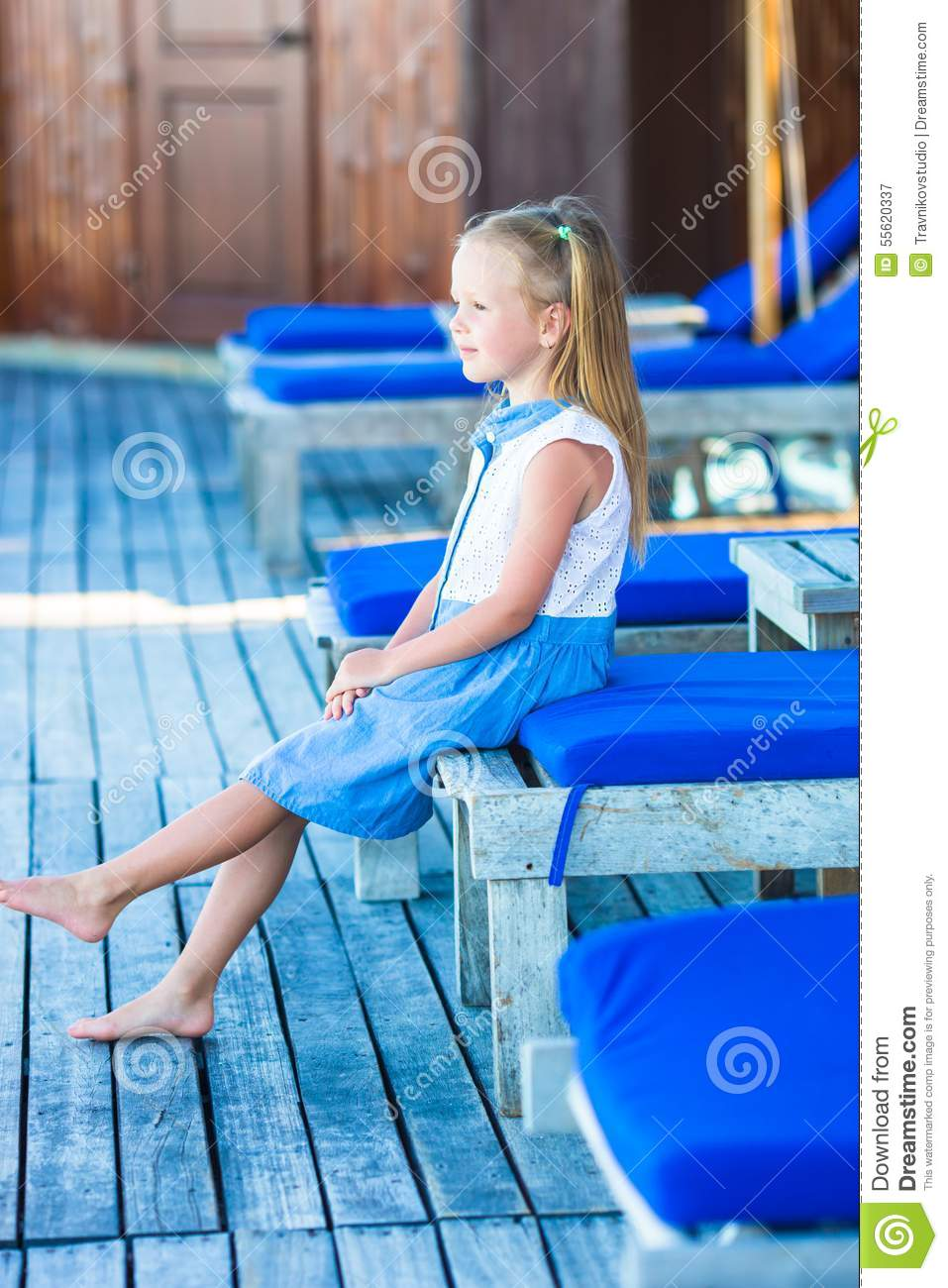 Little adorable girl on beach loungers near the stock - Where is my nearest swimming pool ...