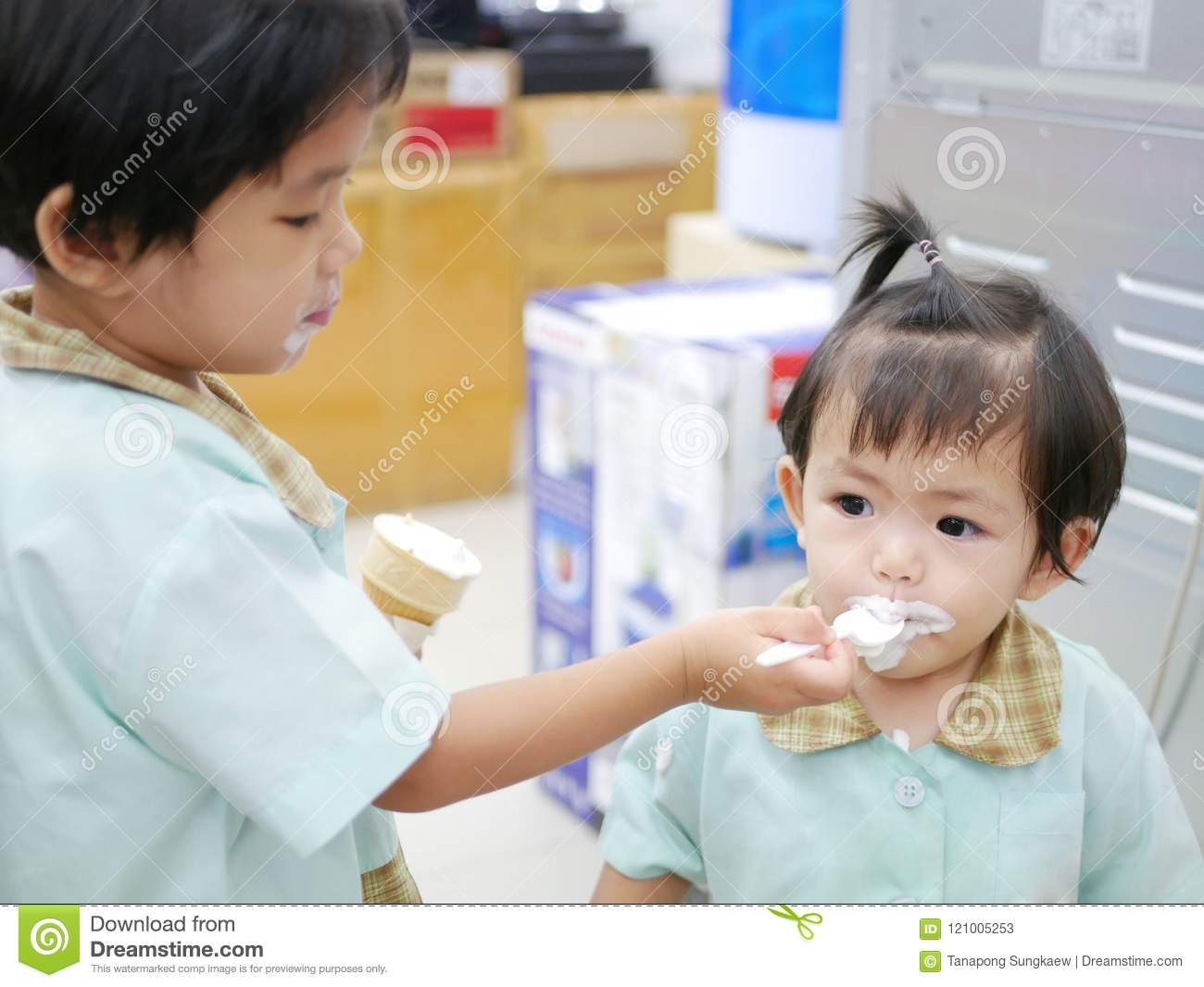 Little Asian baby girl being fed with vanilla ice cream by her older sister