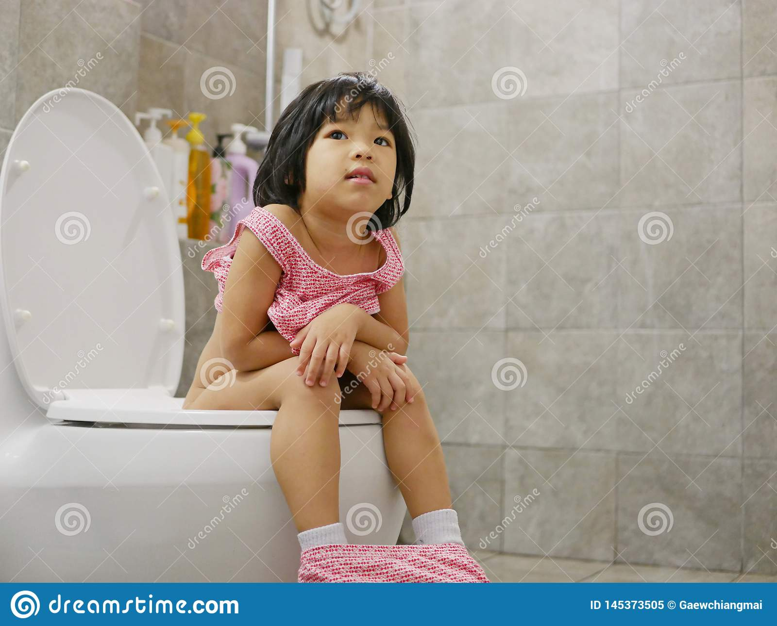 Little Asian baby girl being happy to be able to get on and use adult size toilet bow by herself successfully