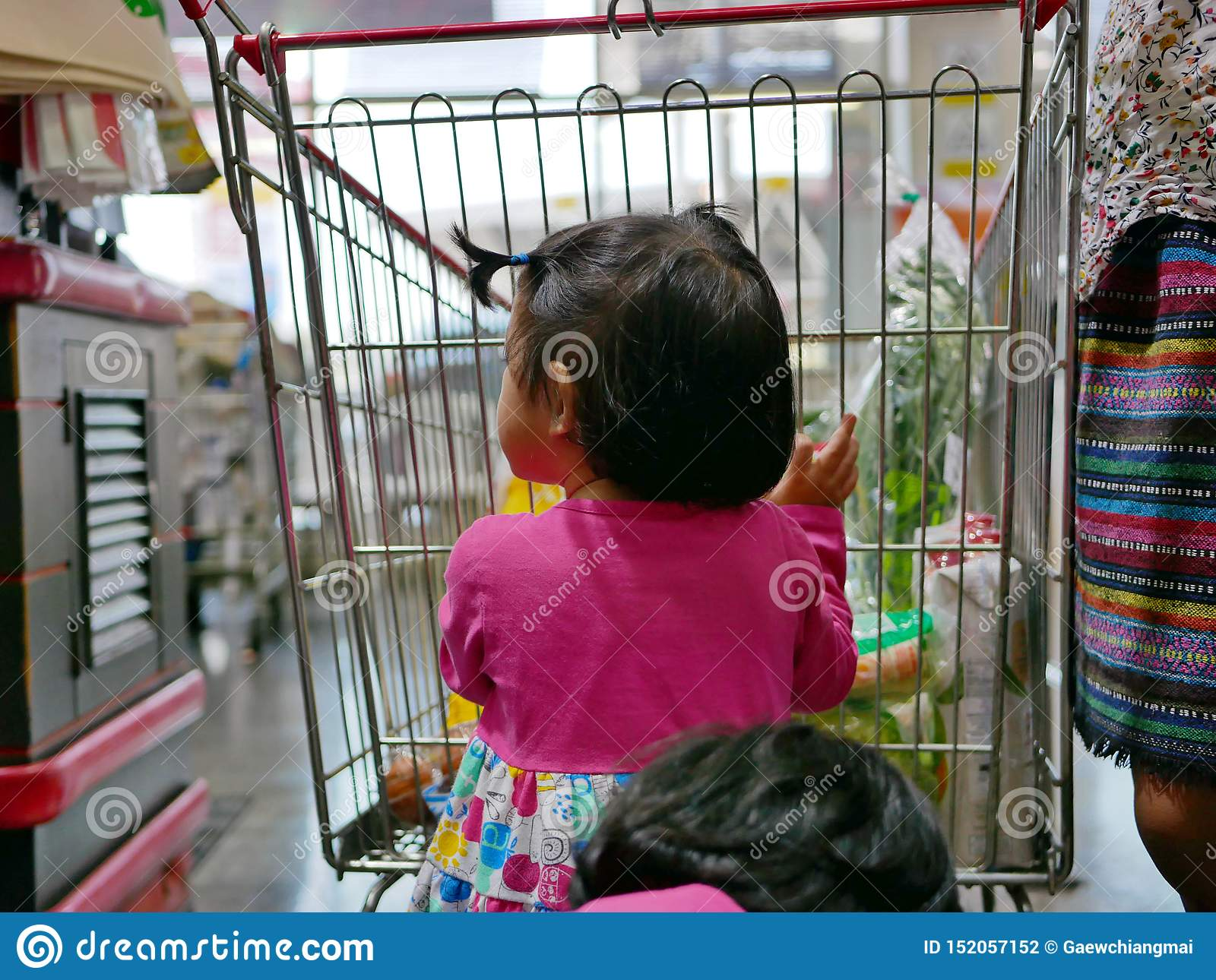 Little Asian baby girl helping her mother push a shopping cart at a supermarket