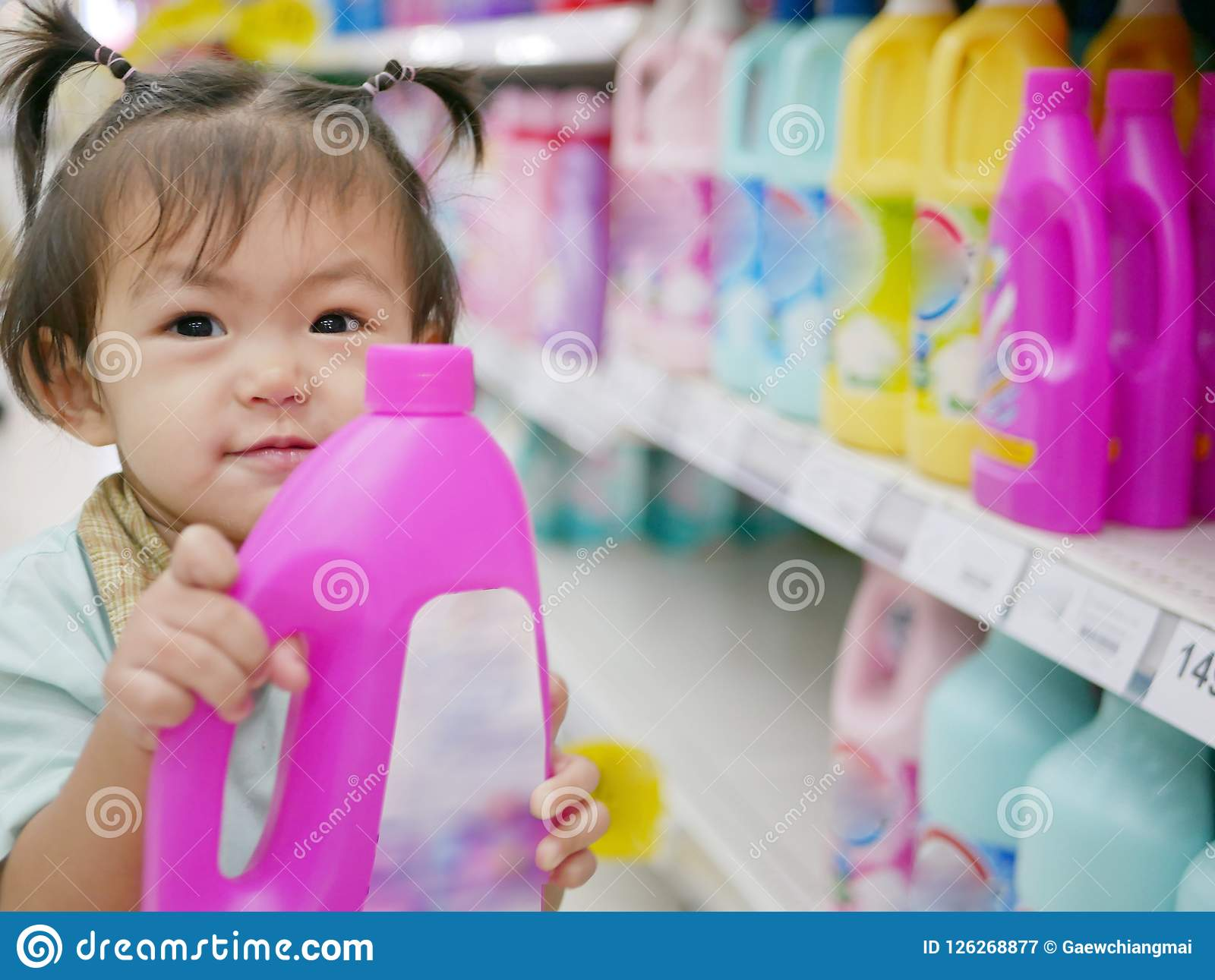 Little Asian baby girl holding a bottle of softener taken from the shelves