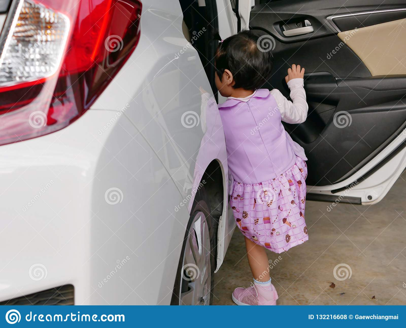 Little Asian baby girl learning to get into the car by herself