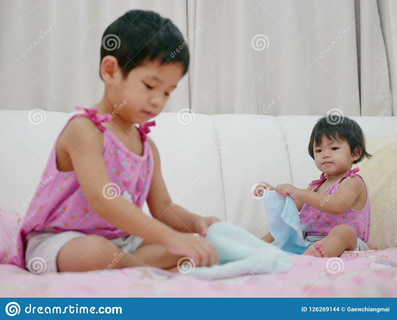 Little Asian baby girl, 18 months old, her older sister folding clothes and try to do the same thing