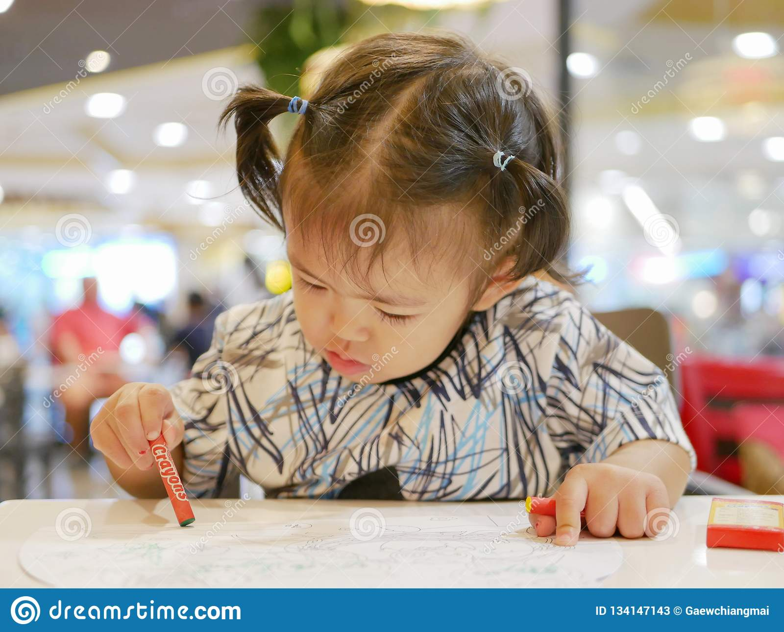 Little Asian Baby Girl Learning To Grasp A Crayon And Do Painting By