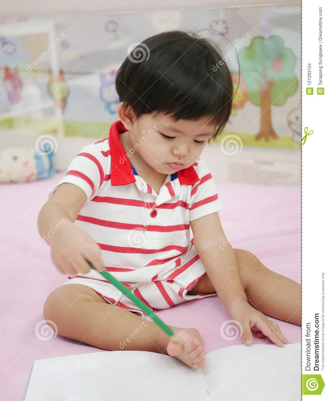 Little asian baby girl learning to hold a pencil and drawing on a