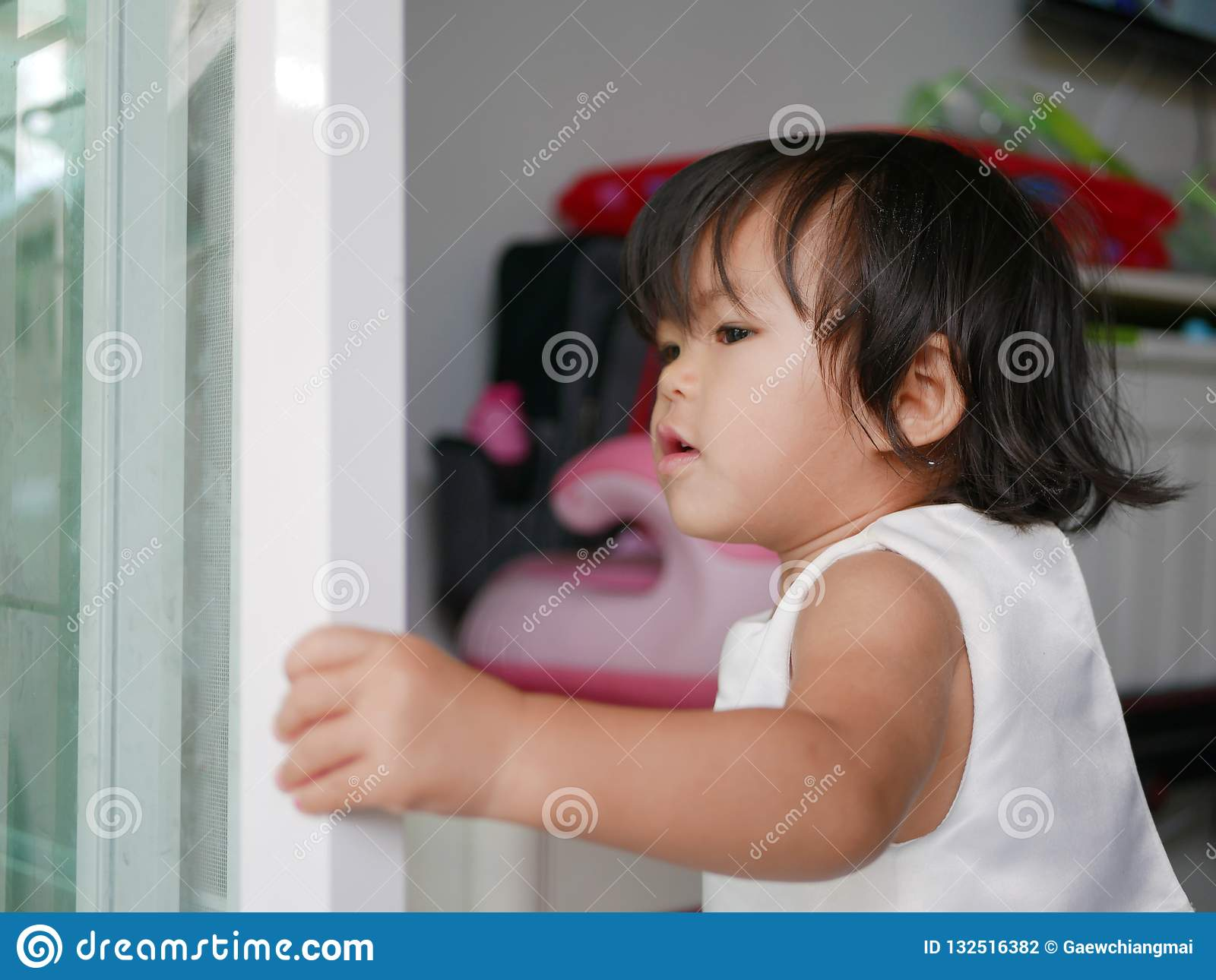 Little Asian baby girl learning to shut / close sliding door by herself