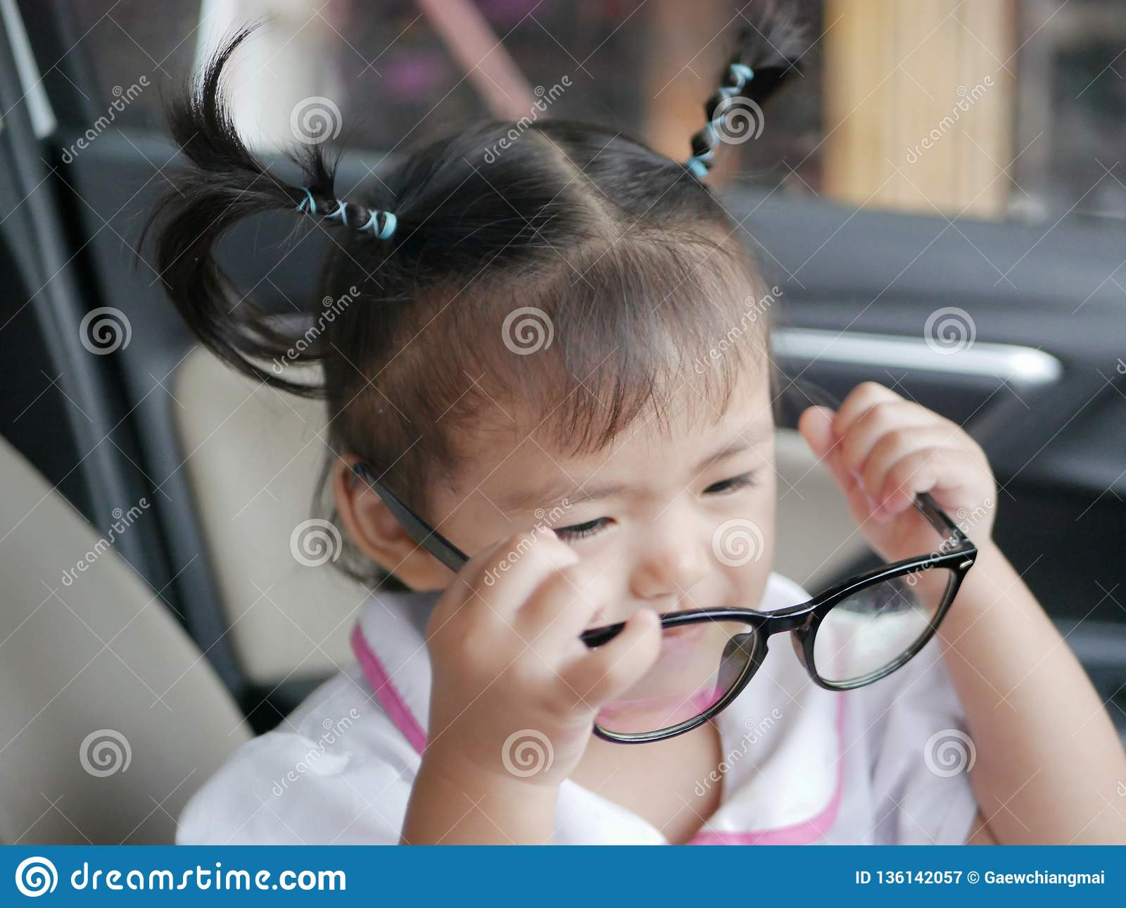 Little Asian baby girl taking off eyeglasses, after trying to put them on