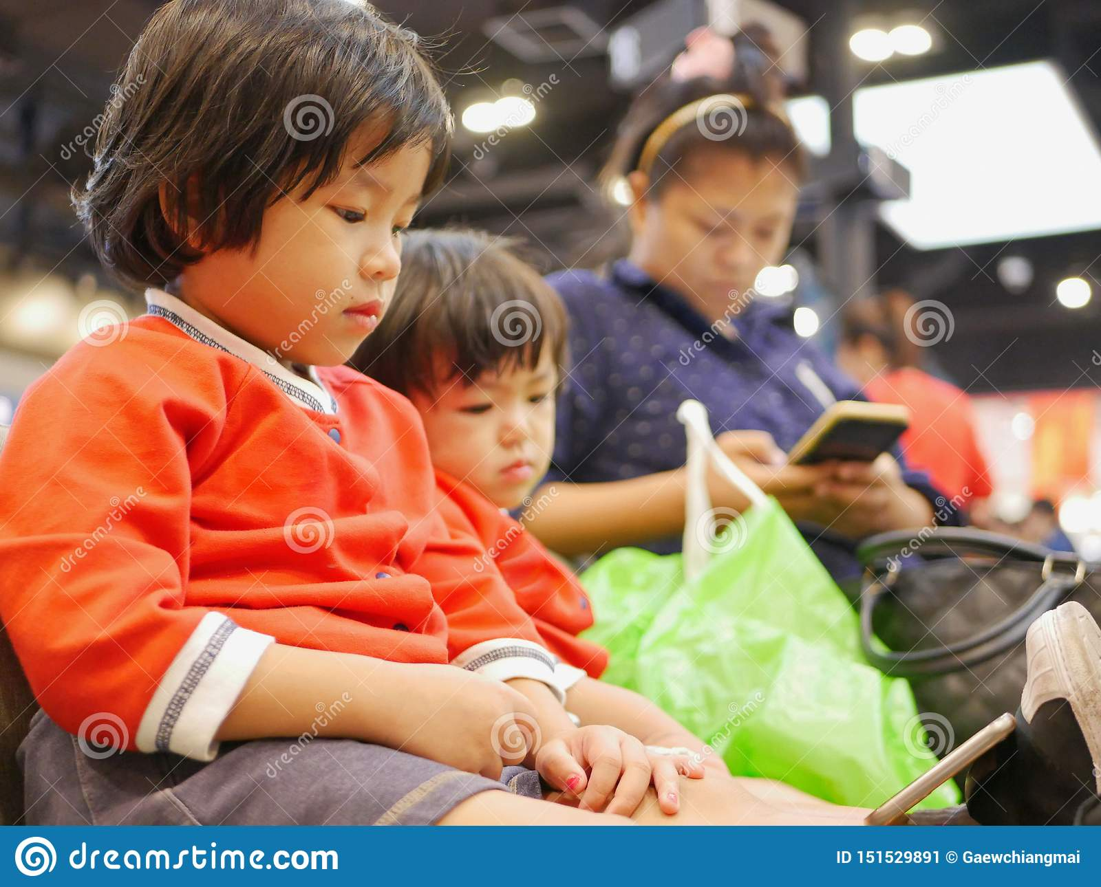 Little Asian baby girl, together with her younger sister, watching a smartphone, same as her mom, sitting and waiting for a queue