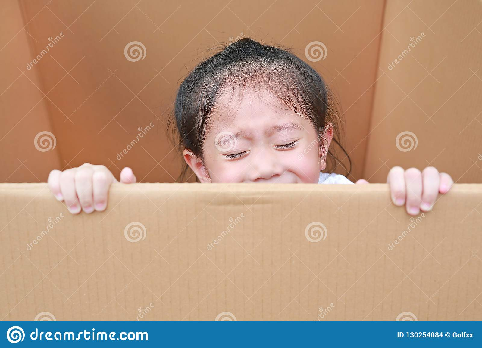 Little Asian child girl playing peekaboo and lie in big cardboard box.