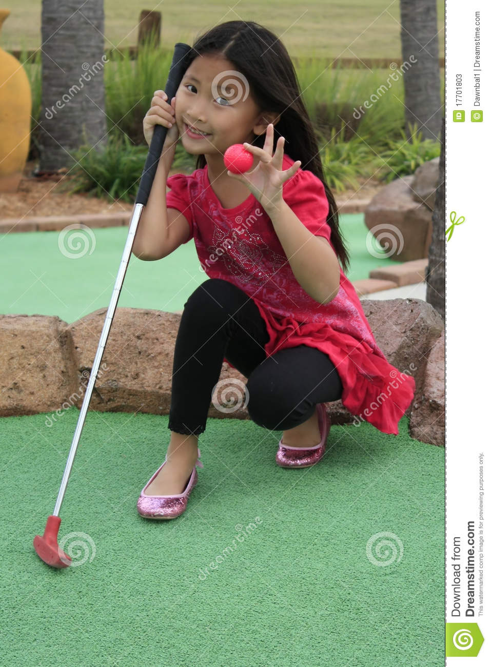 little girl playing mini golf