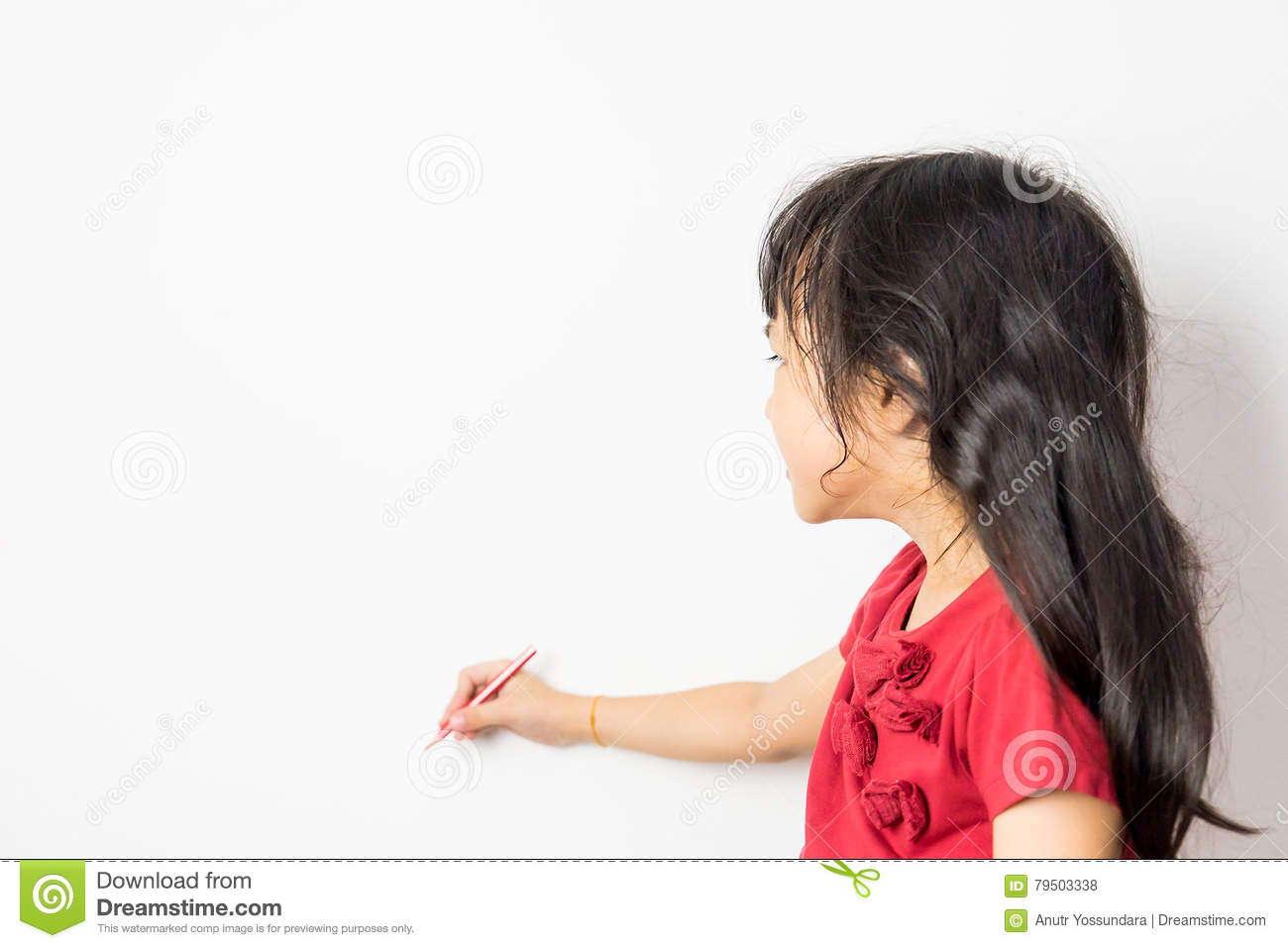 Little Asian girl is writing on a white wall