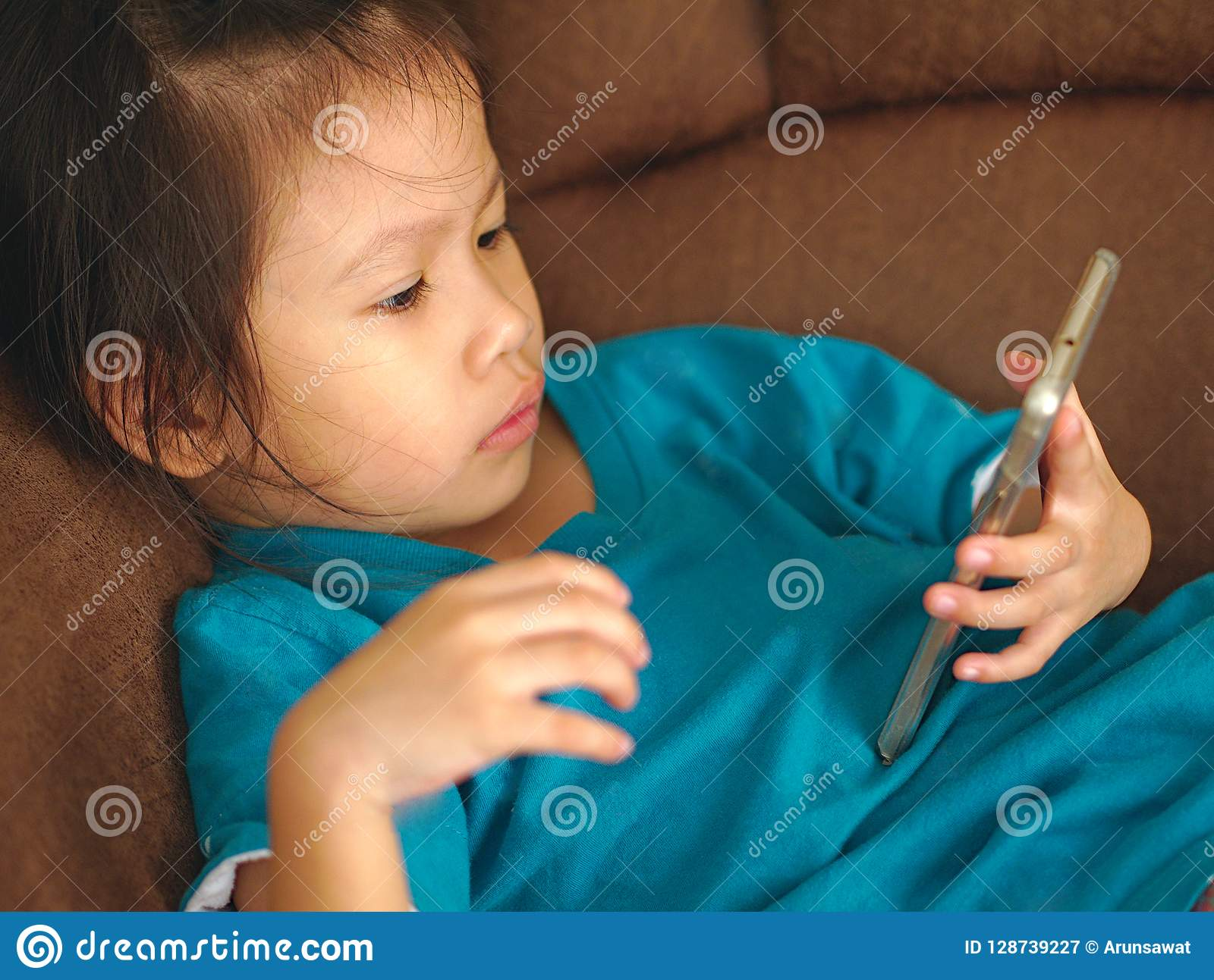 Brilliant Little Asian Kid Using Smartphone On Sofa Bed Look Gmtry Best Dining Table And Chair Ideas Images Gmtryco