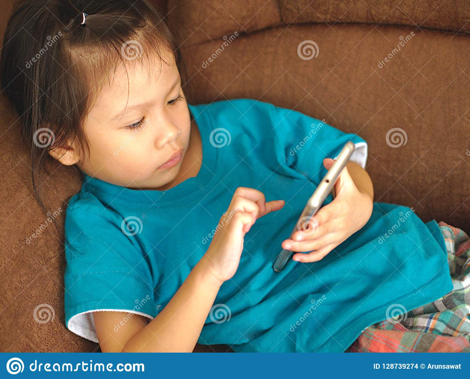 Prime Little Asian Kid Using Smartphone On Sofa Bed Look Gmtry Best Dining Table And Chair Ideas Images Gmtryco