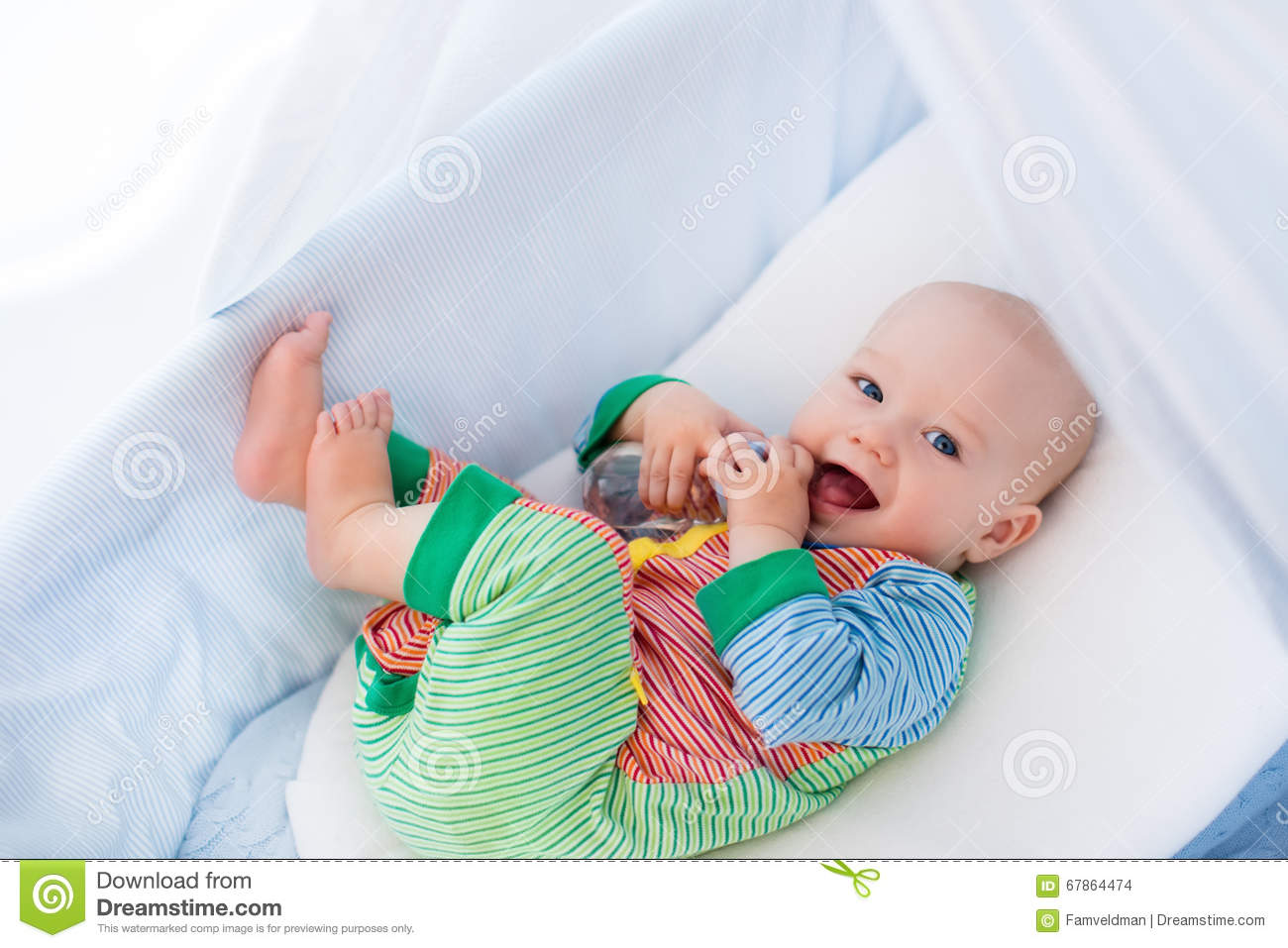 89f90f162f Funny baby in colorful pajamas with bottle drinking water or milk in white  crib with canopy. Healthy nutrition for kids. Nursery interior and bedding  for ...