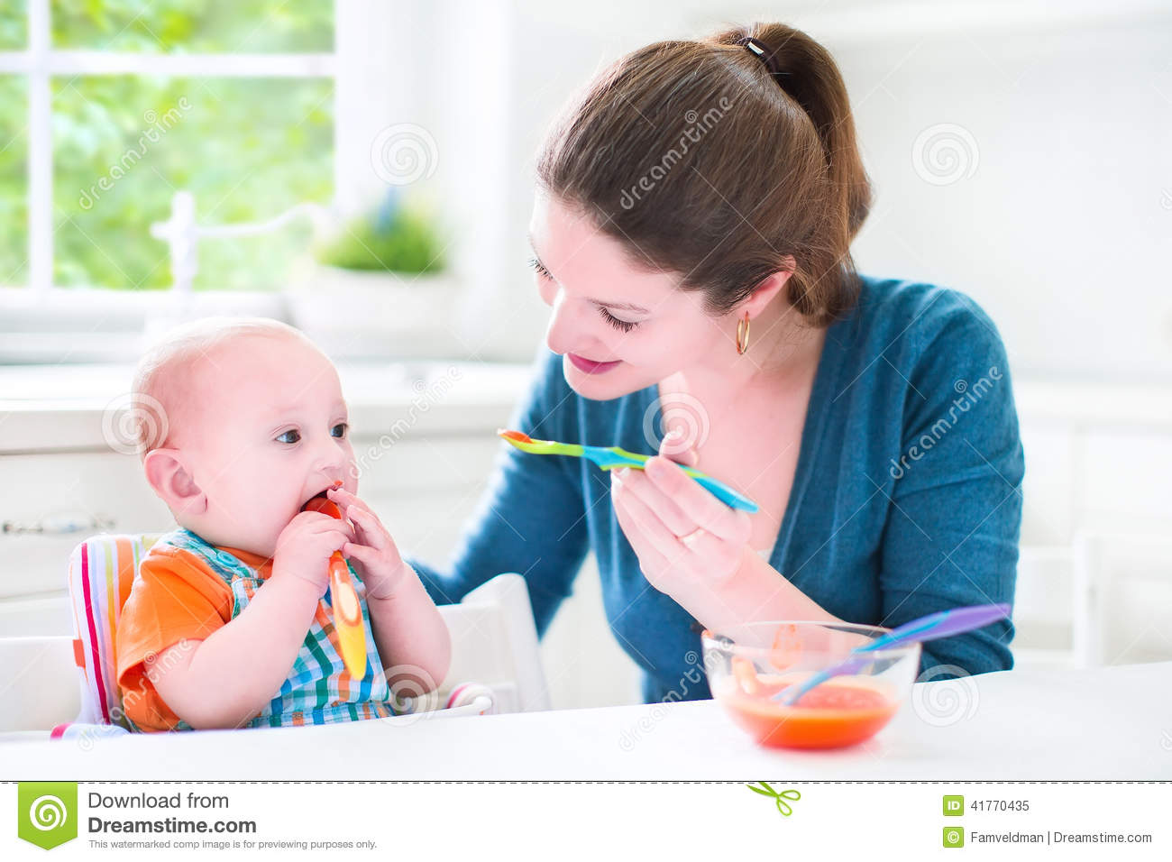 Little Baby Boy Eating His First Solid Food Stock Photo