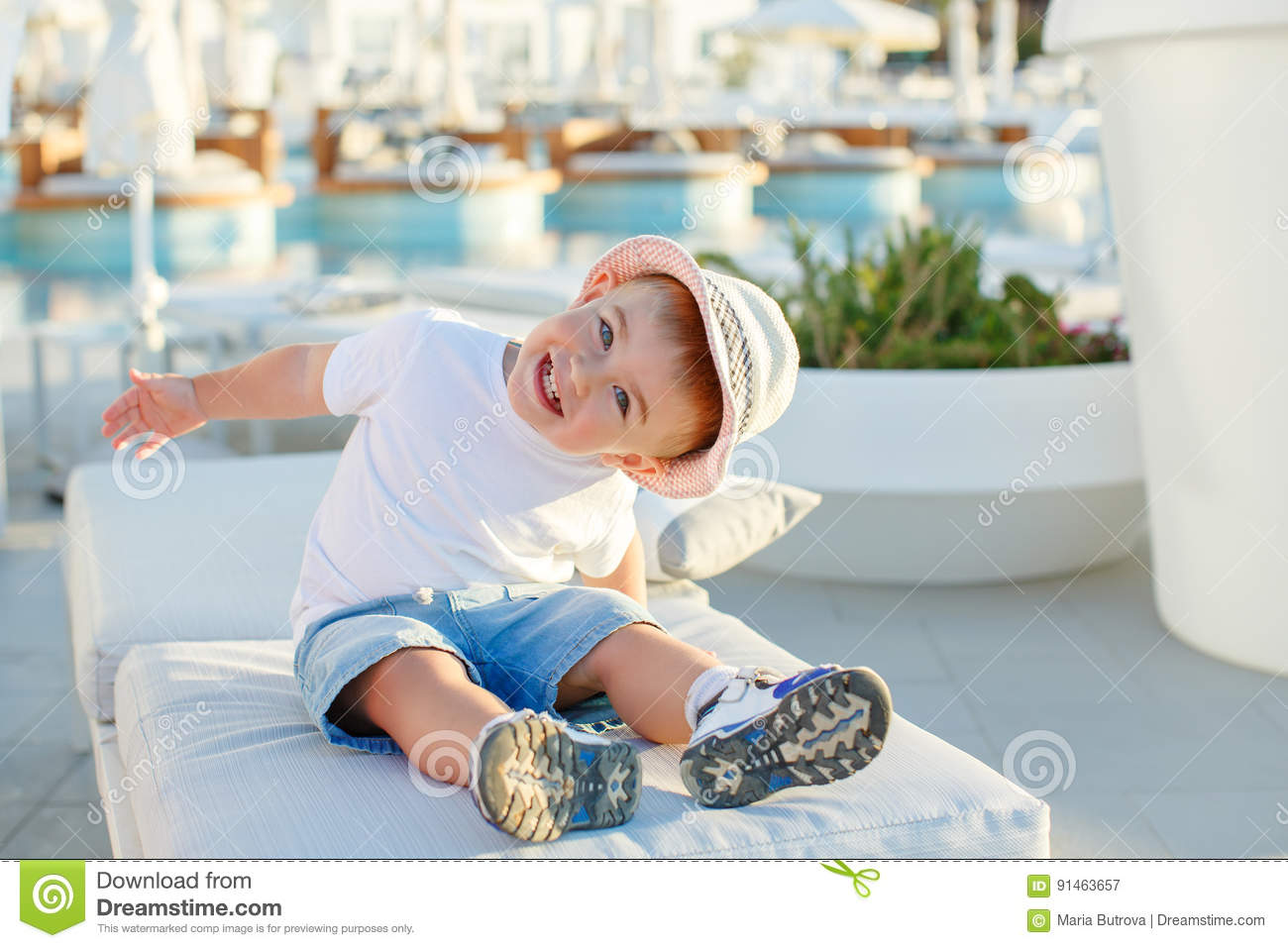Little Baby Boy In A Hat Sitting On A Background Of The Pool And ... 522a1f0807e