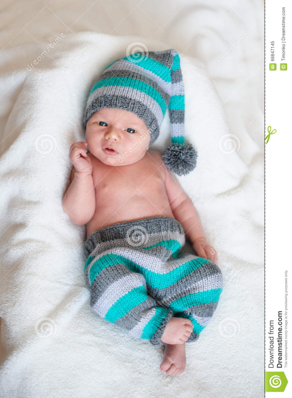Little Baby Boy In A Knitted Hat Lying On The White Bed Stock Image ... e6f044ec9706