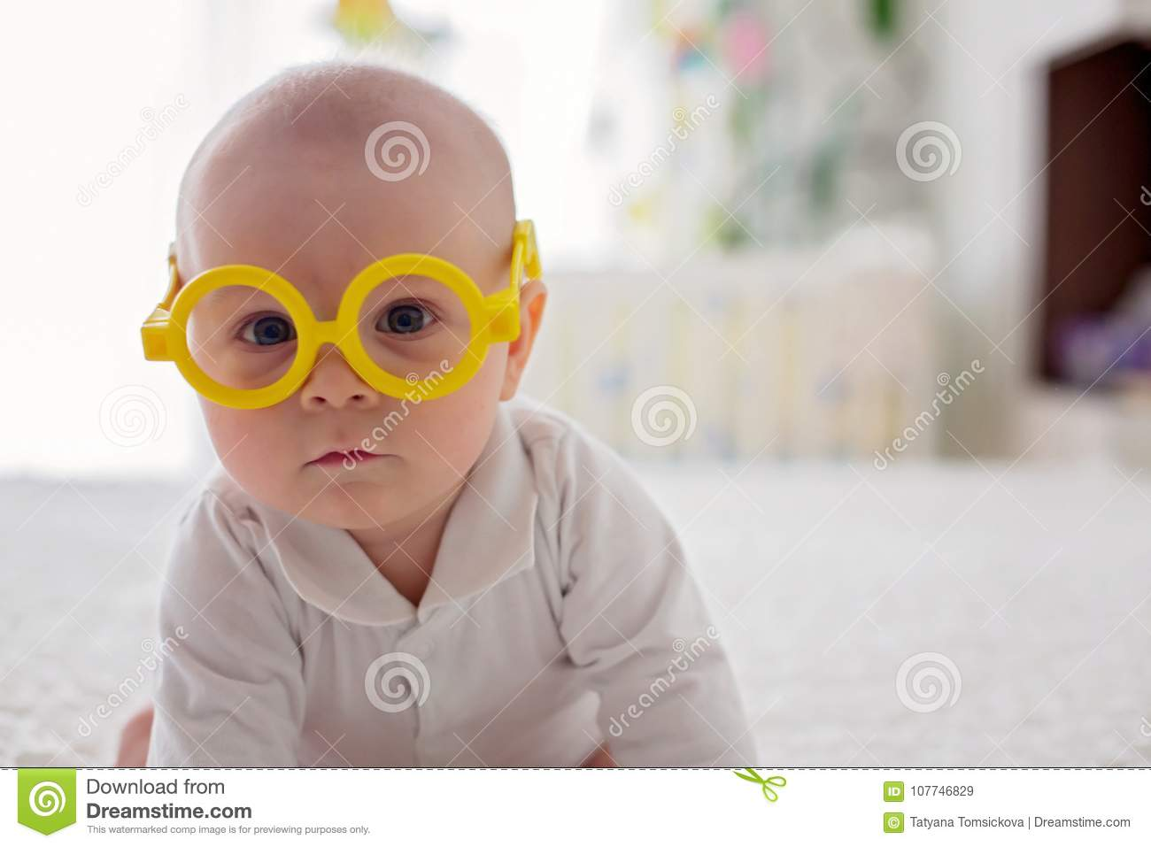 Little baby boy, toddler, playing at home with funny eye glasses