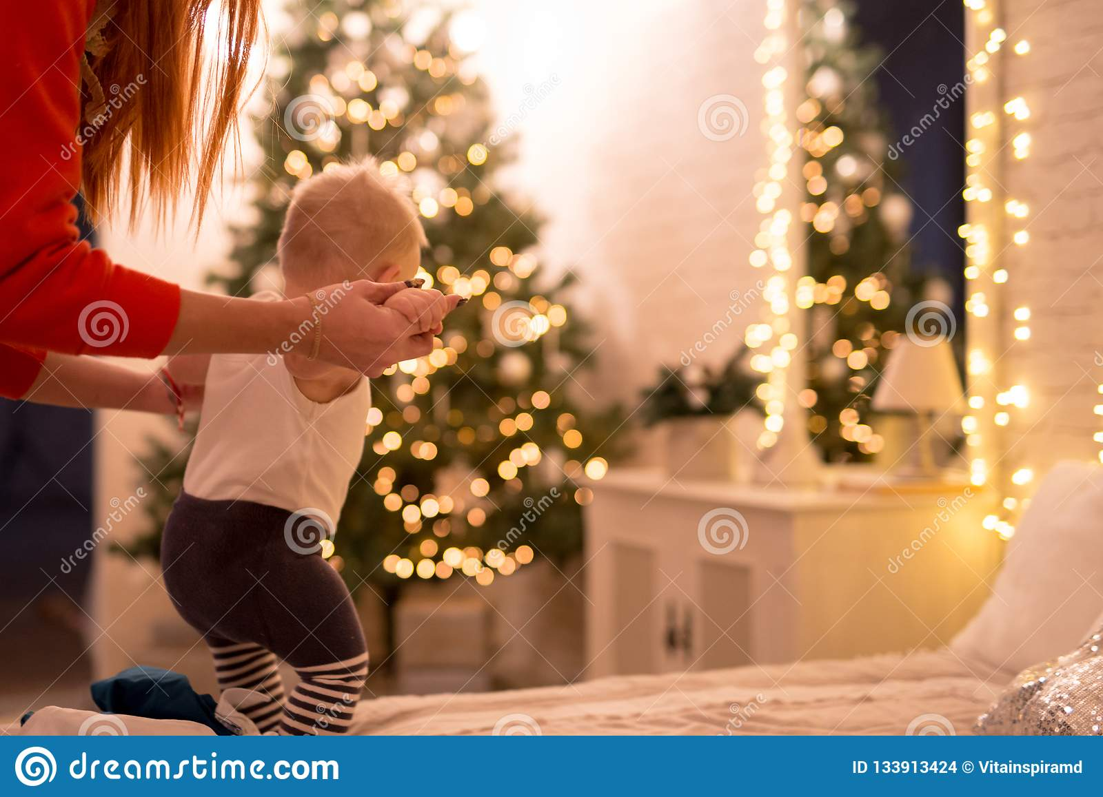 Little baby boy 1 year old learning how to walk in a decorated New Year house. Mom hold by the hands of her son.