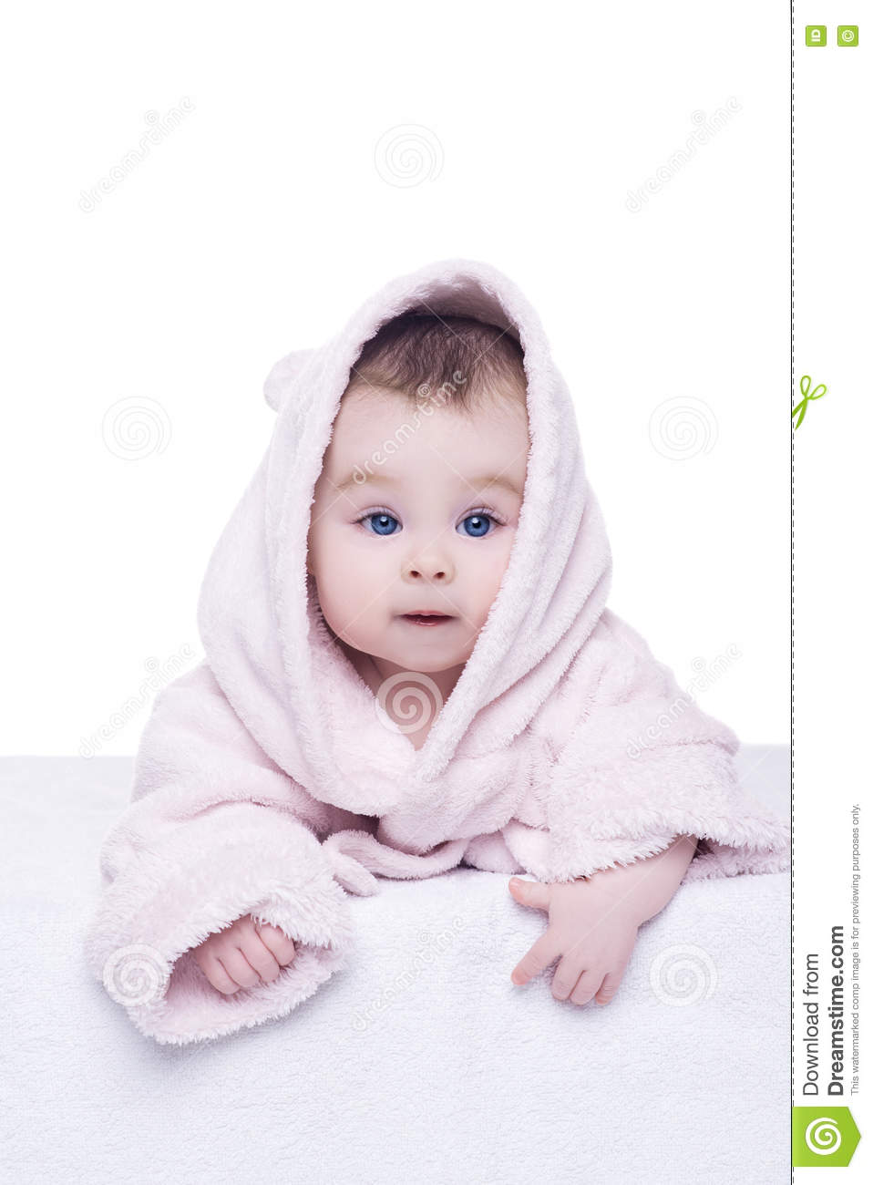 Little baby girl with blue eyes in pink bathrobe lying on her be