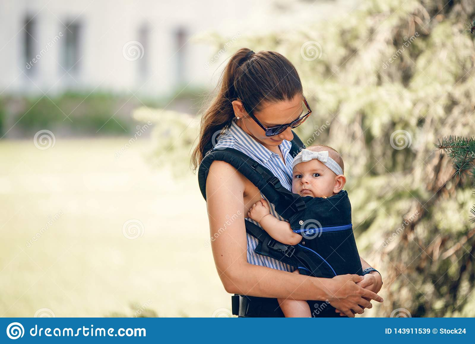Little Baby Girl And Her Mother Walking Outside Babywearing In The