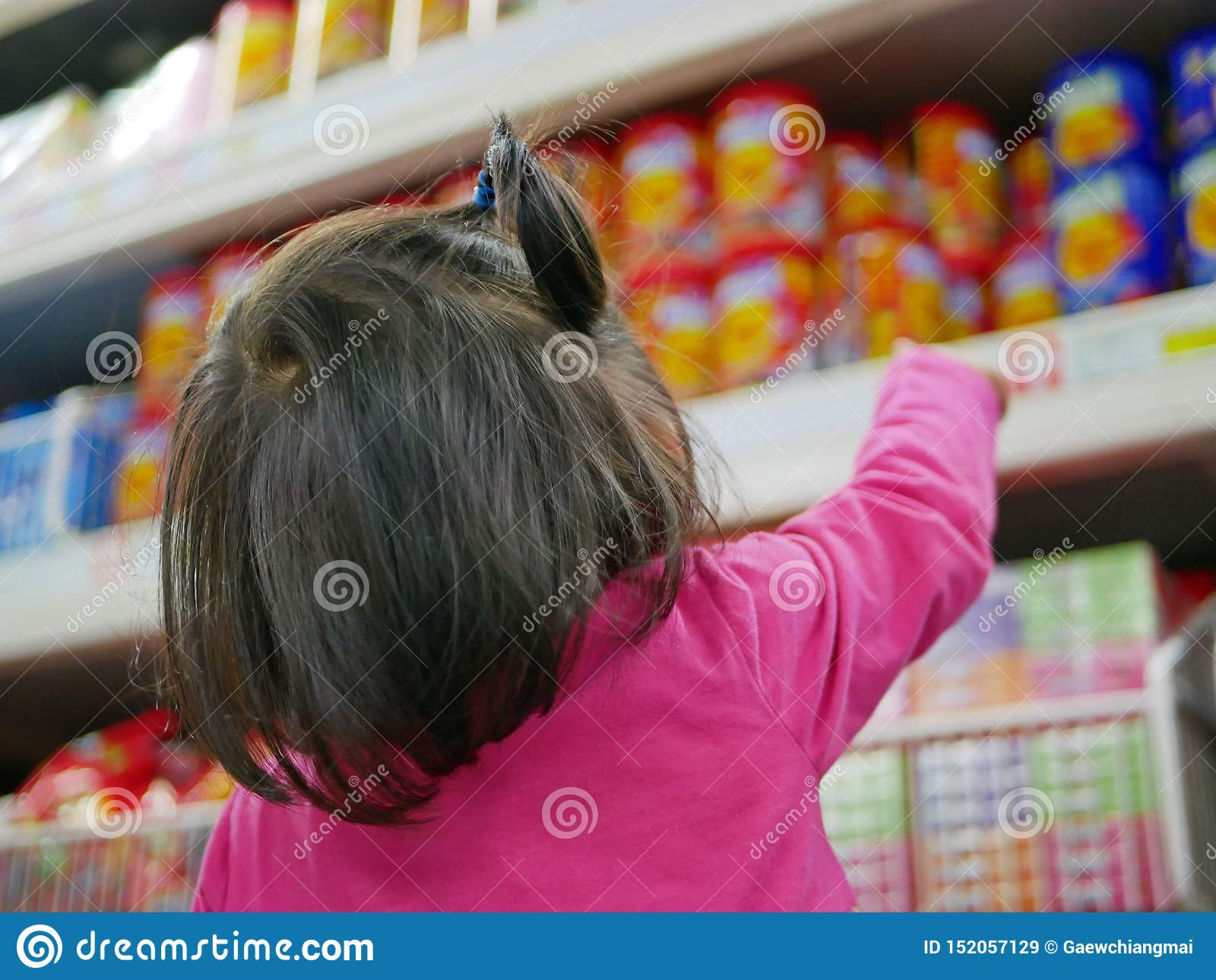 Little baby girl pointing at colorful snacks / candies on the shelves in a supermarket, wanting her parents to buy some for her