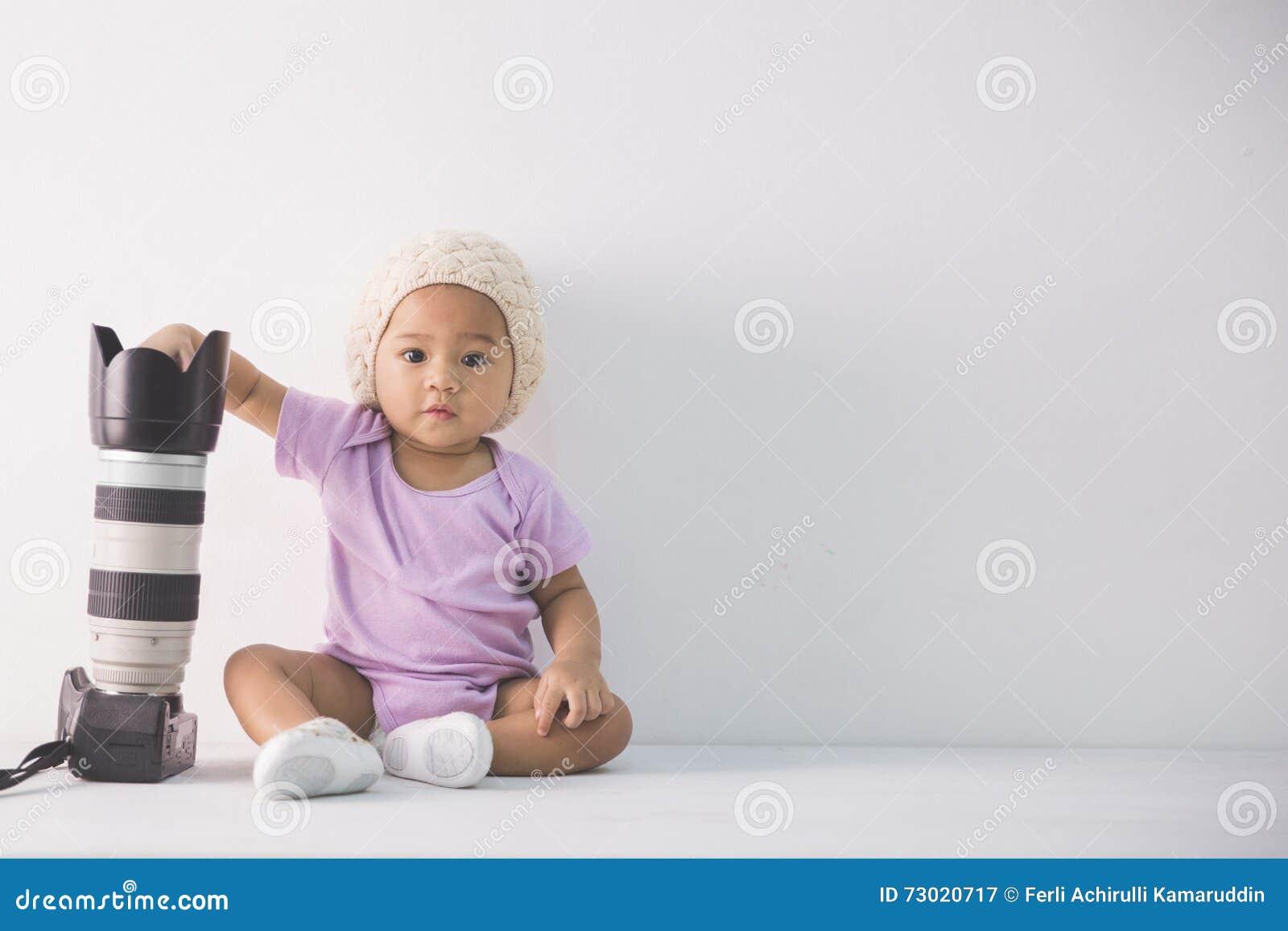 Little baby girl sitting on the floor holding dslr camera