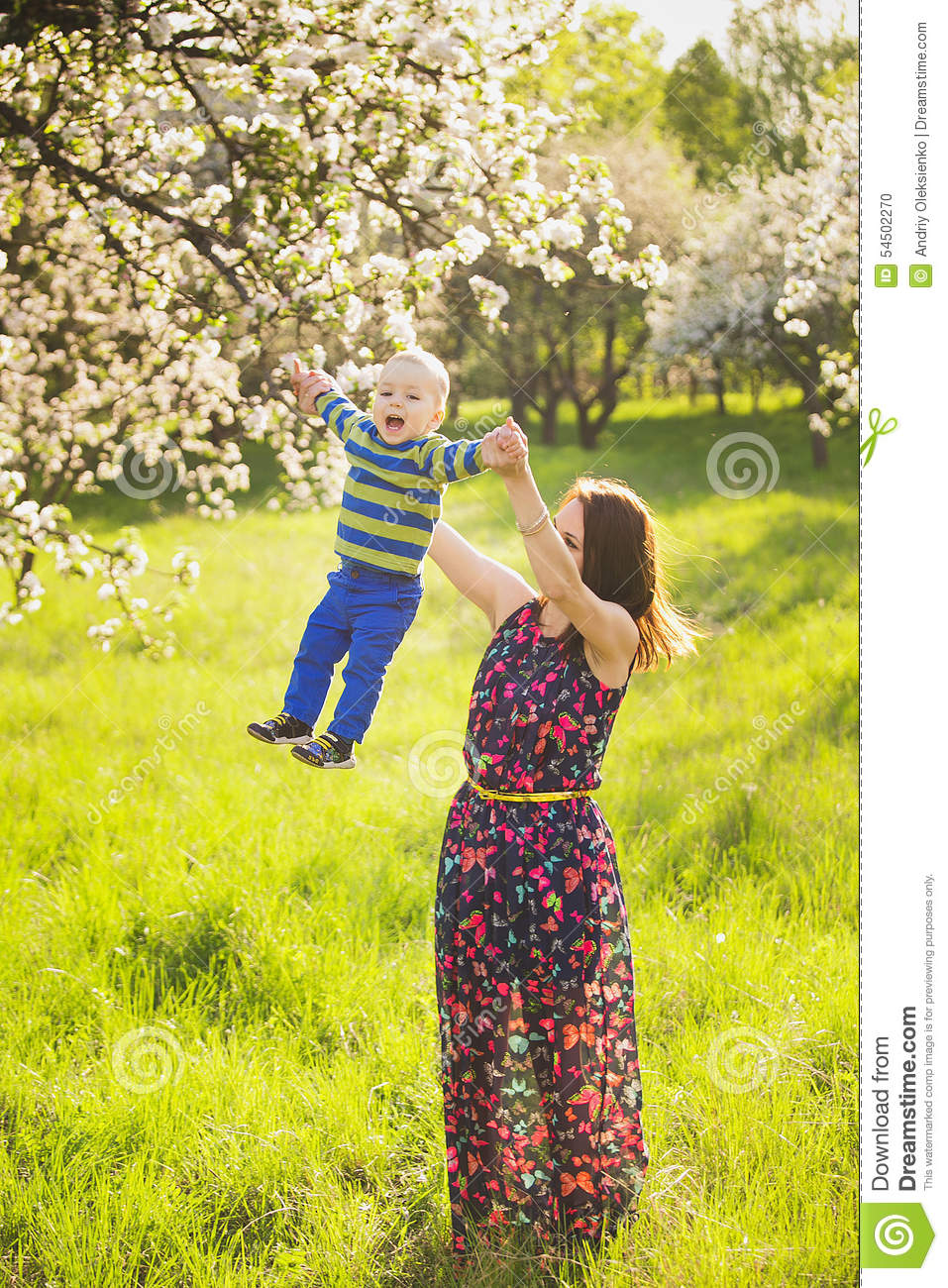 Little baby on hands of mother. woman playing with child outside